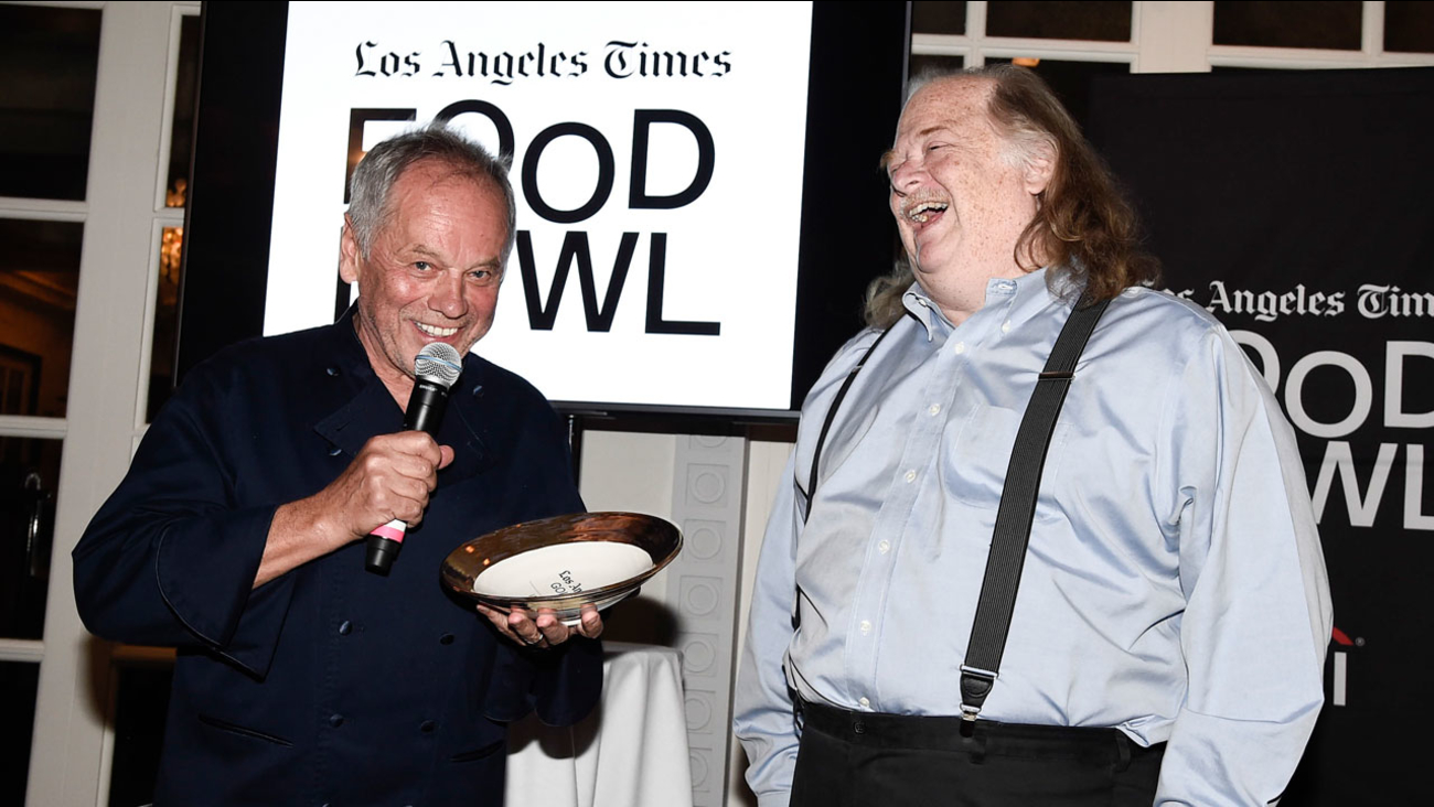 Chef Wolfgang Puck, left, accepts his Gold Award as Los Angeles Times Food Critic Jonathan Gold looks on at the Los Angeles Times Food Bowl Gold Award Party at Spago on May 8, 2017