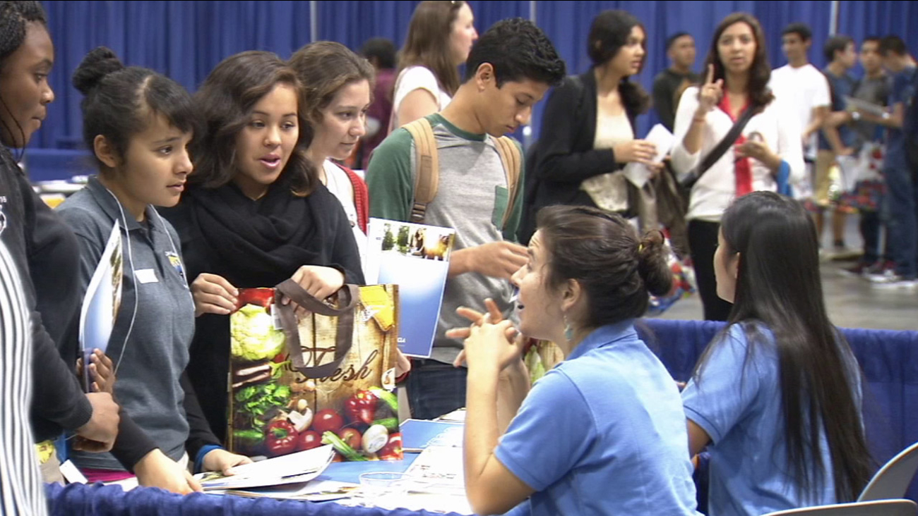 A woman speaks to high school kids at the Cash for College fair in Los Angeles on Wednesday, Nov. 5, 2014.