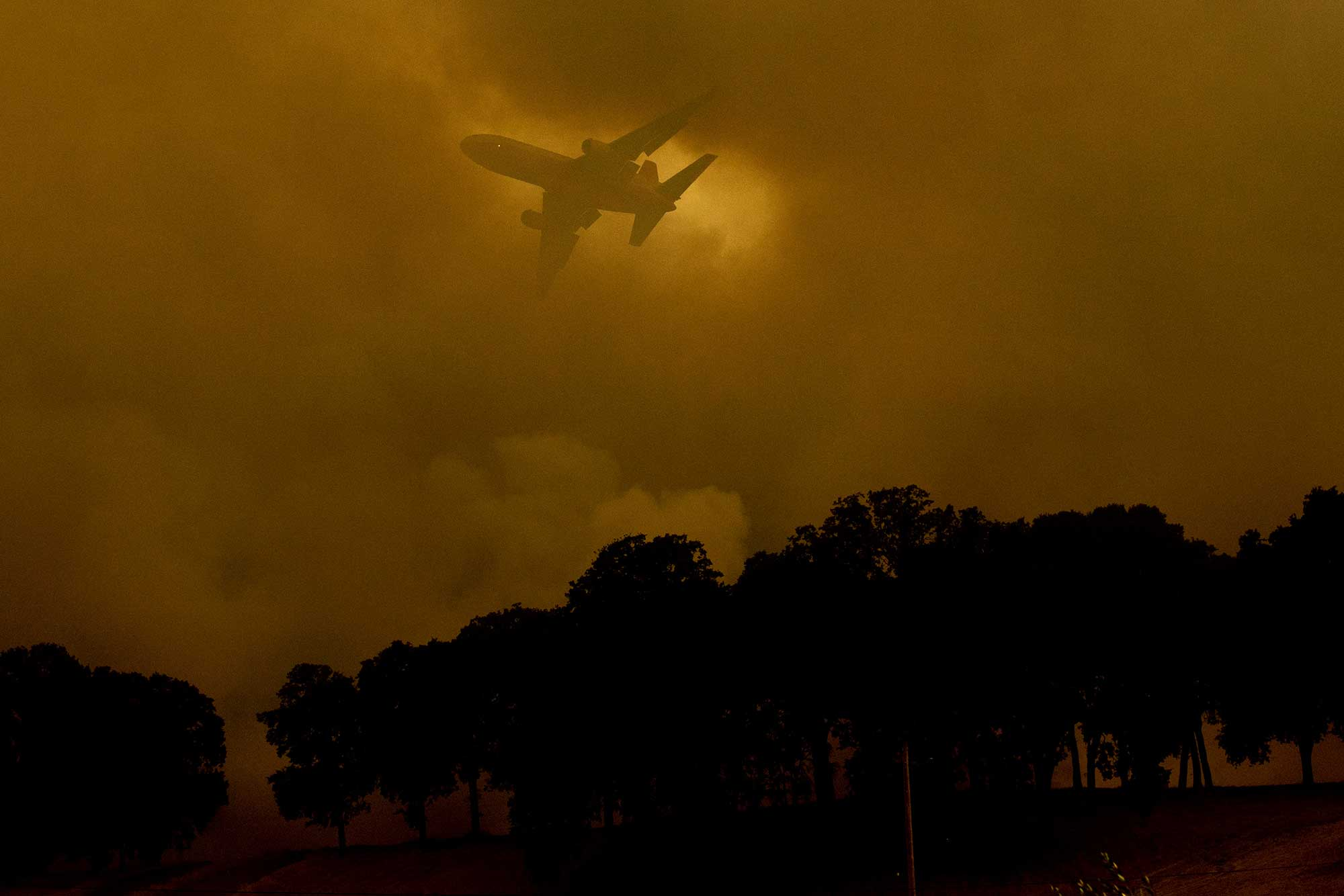 <div class='meta'><div class='origin-logo' data-origin='none'></div><span class='caption-text' data-credit='Noah Berger/AP Photo'>An air tanker passes behind a smoke plume while battling the River Fire in Lakeport, Calif., on Monday, July 30, 2018.</span></div>