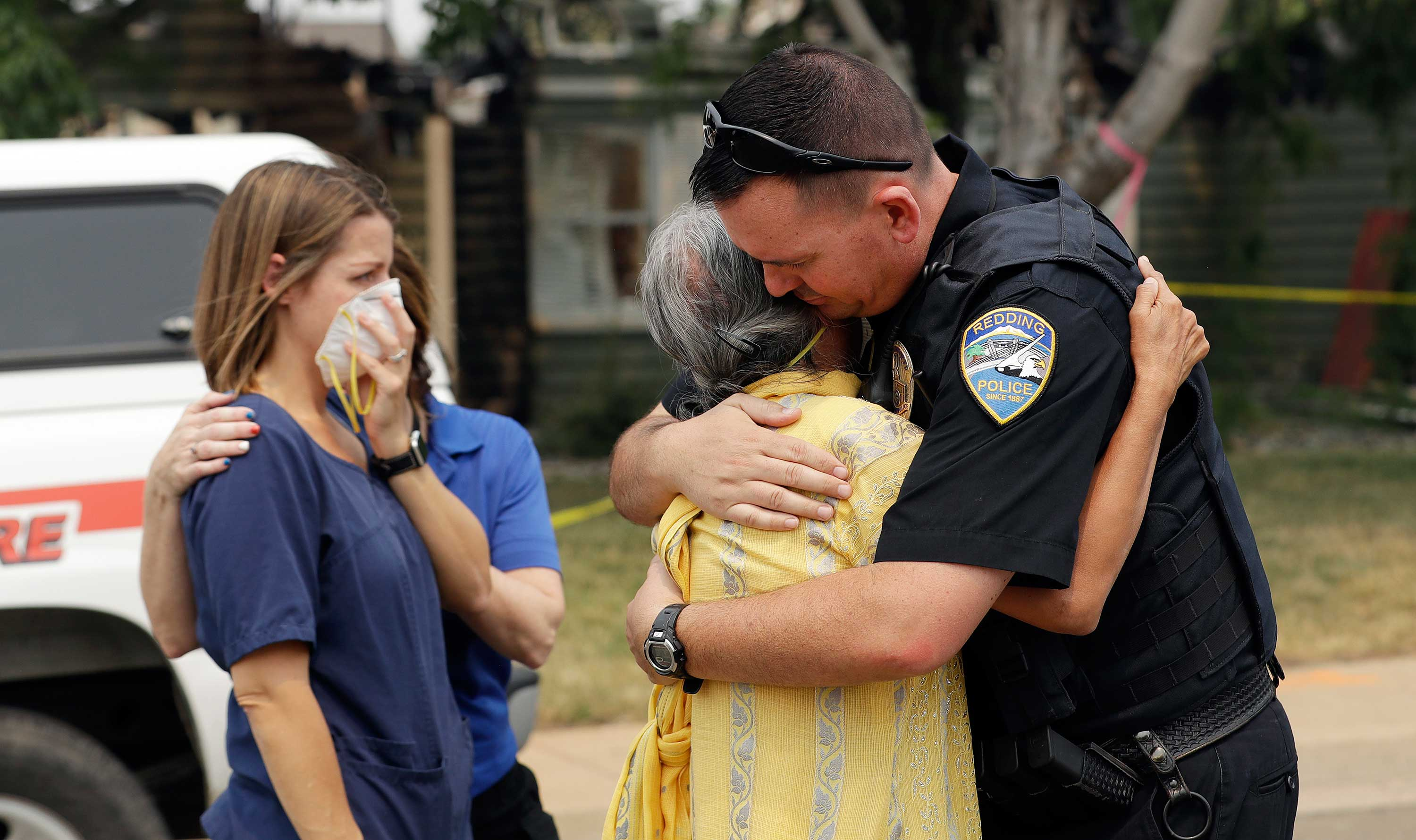 <div class='meta'><div class='origin-logo' data-origin='none'></div><span class='caption-text' data-credit='Marcio Jose Sanchez/AP Photo'>Redding Police Dept. officer Brian Berg, right, comforts a resident, center, wishing not to be identified, after she saw her fire-ravaged home for the first time Thursday, Aug. 2.</span></div>