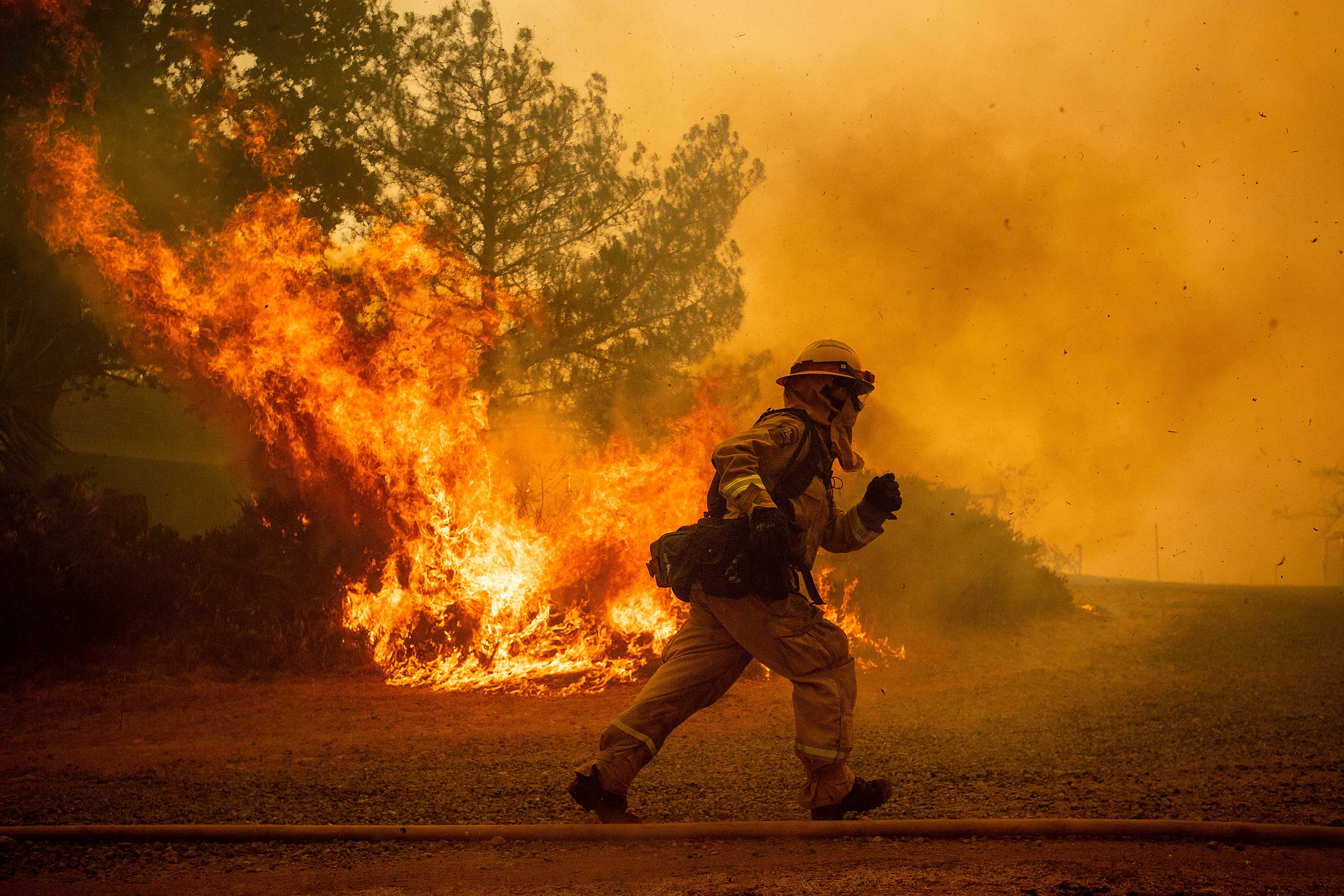 <div class='meta'><div class='origin-logo' data-origin='none'></div><span class='caption-text' data-credit='Noah Berger/AP Photo'>A firefighter runs while trying to save a home as a wildfire tears through Lakeport, Calif., Tuesday, July 31, 2018.</span></div>