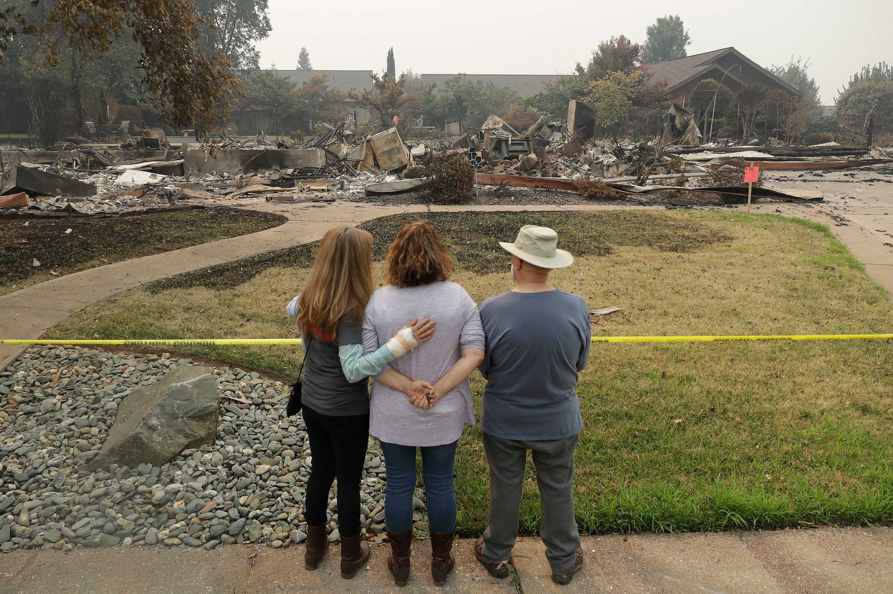 <div class='meta'><div class='origin-logo' data-origin='none'></div><span class='caption-text' data-credit='Marcio Jose Sanchez/AP Photo'>Tim Smith, at right, gets a first look at his wildfire-ravaged home alongside his daughter, Suzie Scatena, center, and aid worker Deborah Coombs Thursday, Aug. 2.</span></div>