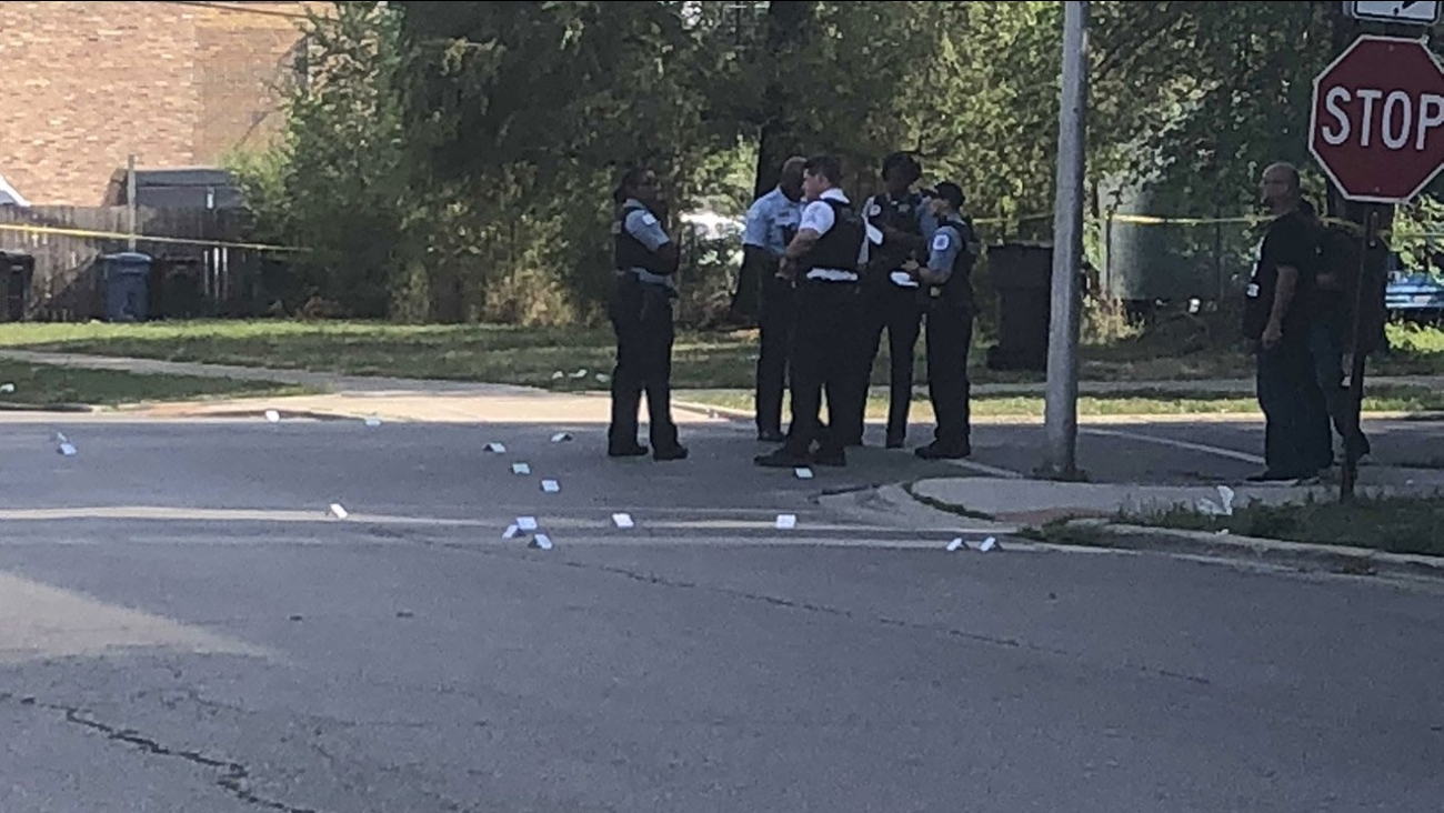 Police officers stand on a street corner in Lawndale where three men were shot.