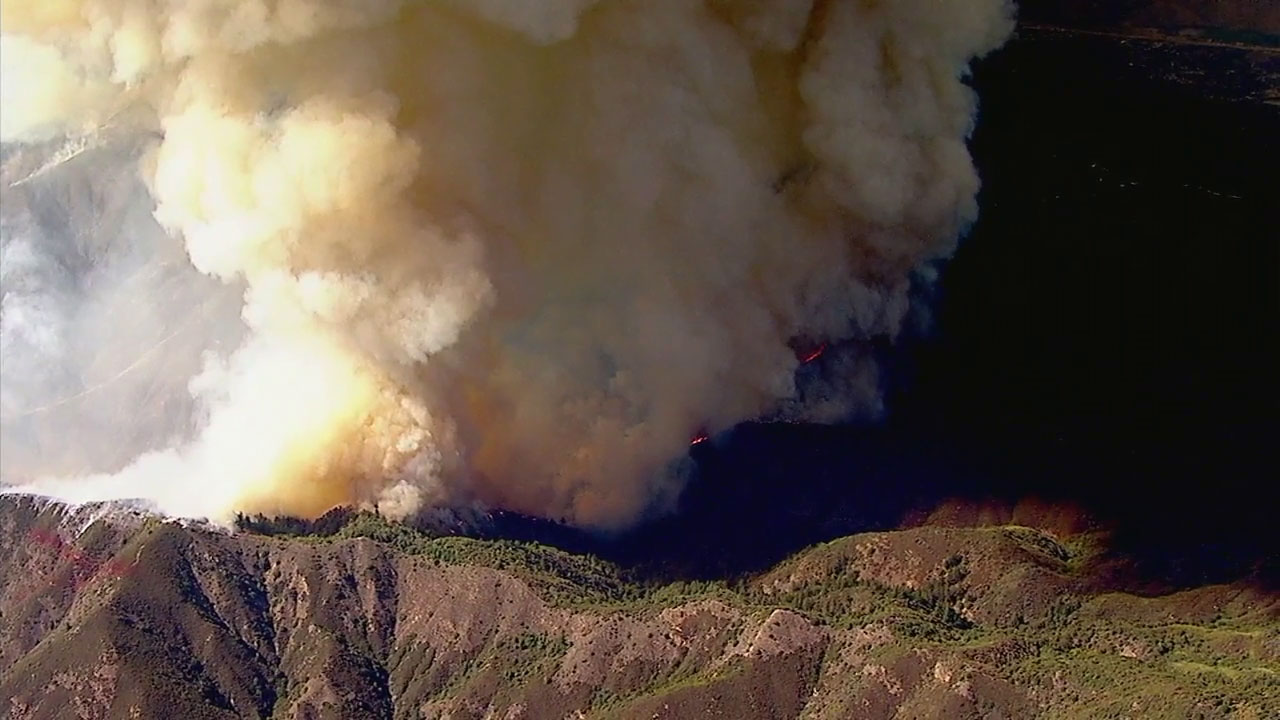 A plume of smoke goes up in the air as brush burns in the Holy Fire in the Trabuco Canyon area on Monday, Aug. 6, 2018.
