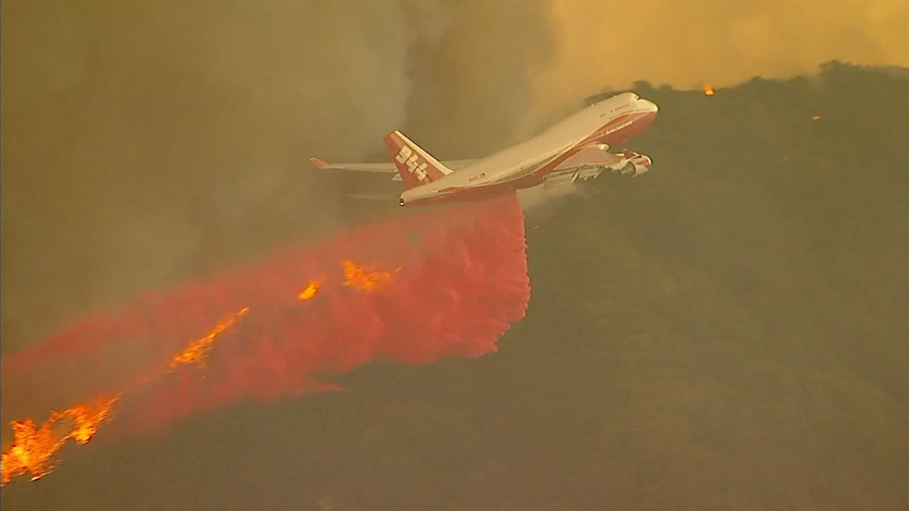 An airplane fire retardant drop is shown as firefighters battle a 4,000-acre brush fire in Orange County's side of the Cleveland National Forest.