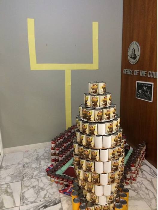 "<div class=""meta image-caption""><div class=""origin-logo origin-image ""><span></span></div><span class=""caption-text"">OCC TACKLES HUNGER: Office of the County Counsel built the Coliseum and a giant football out of cans. This display was made from 806.25 pounds of food.</span></div>"