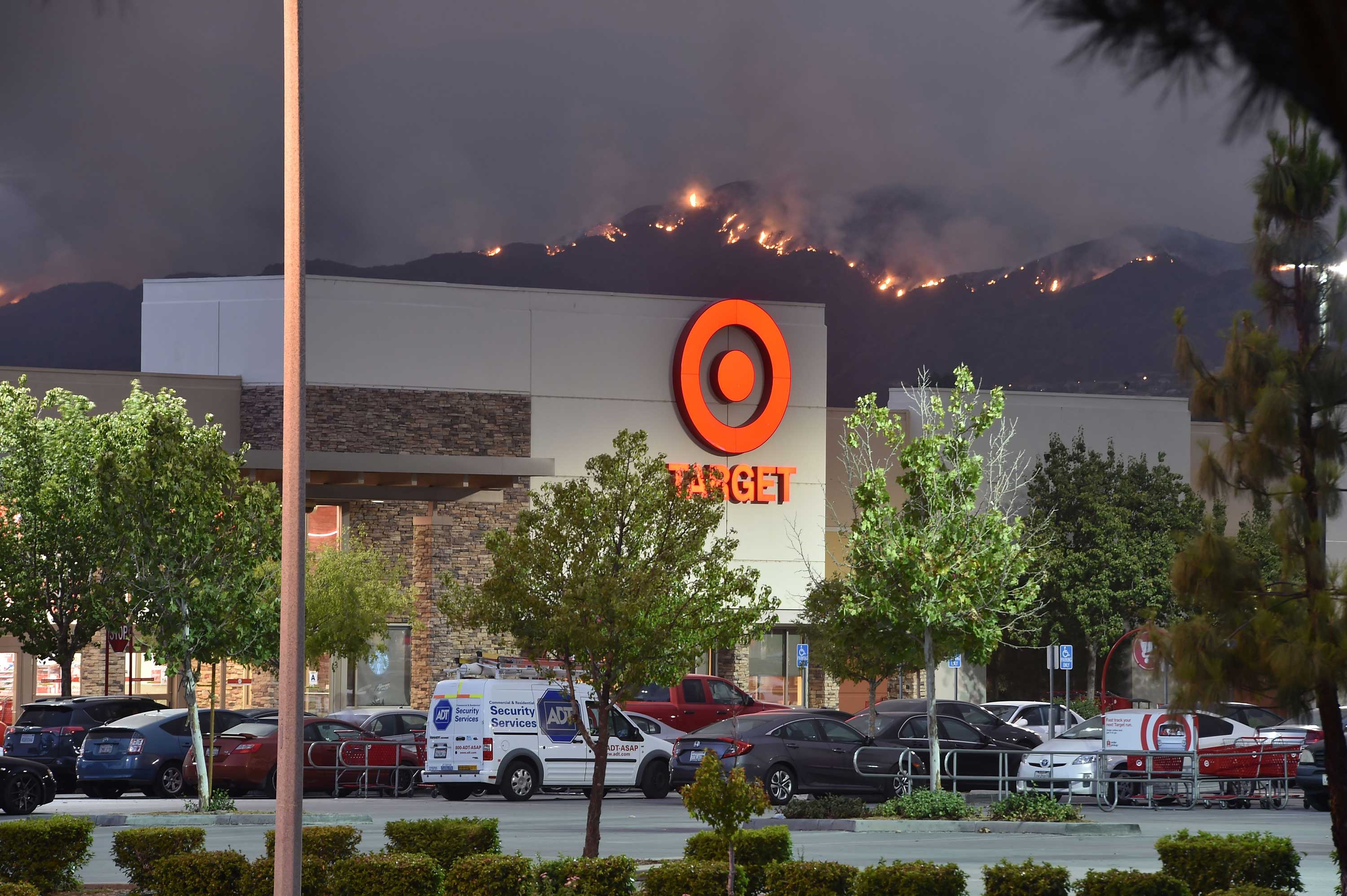 "<div class=""meta image-caption""><div class=""origin-logo origin-image none""><span>none</span></div><span class=""caption-text"">The Holy Fire burns in the distant behind a Target store, near Lake Elsinore, California on August 8, 2018. (ROBYN BECK/AFP/Getty Images)</span></div>"