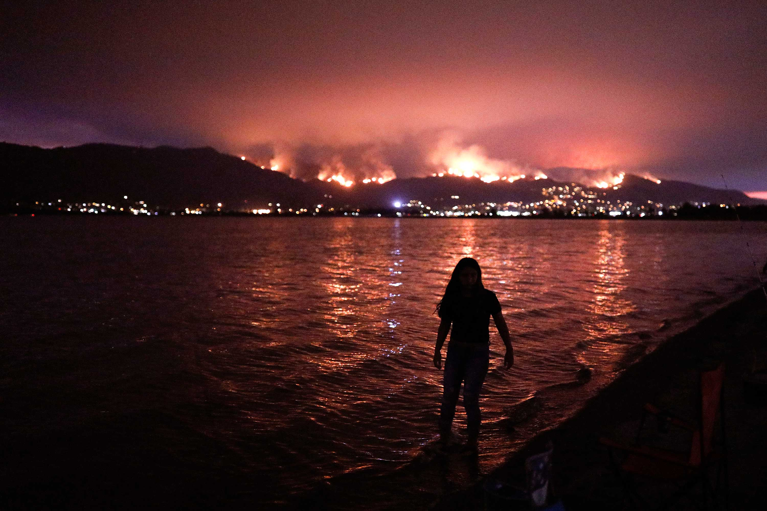 <div class='meta'><div class='origin-logo' data-origin='none'></div><span class='caption-text' data-credit='Jae C. Hong/AP Photo'>A girl wades through water while watching a wildfire burn in the Cleveland National Forest in Lake Elsinore, Calif., Wednesday, Aug. 8, 2018.</span></div>