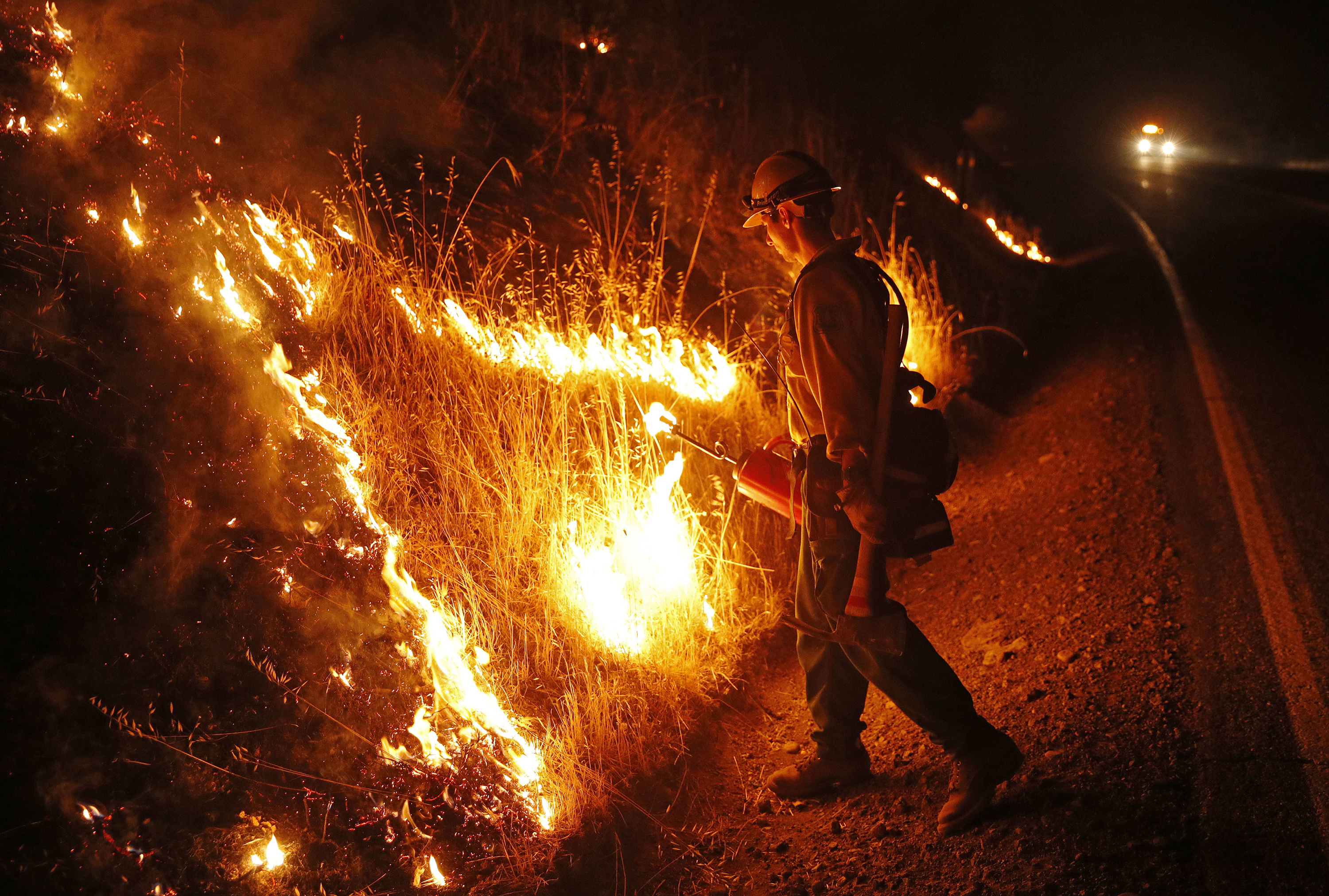 <div class='meta'><div class='origin-logo' data-origin='none'></div><span class='caption-text' data-credit='John Locher/AP Photo'>A firefighter lights a back burn while battling the Hat Fire, Thursday, Aug. 9, 2018, near Fall River Mills, Calif.</span></div>