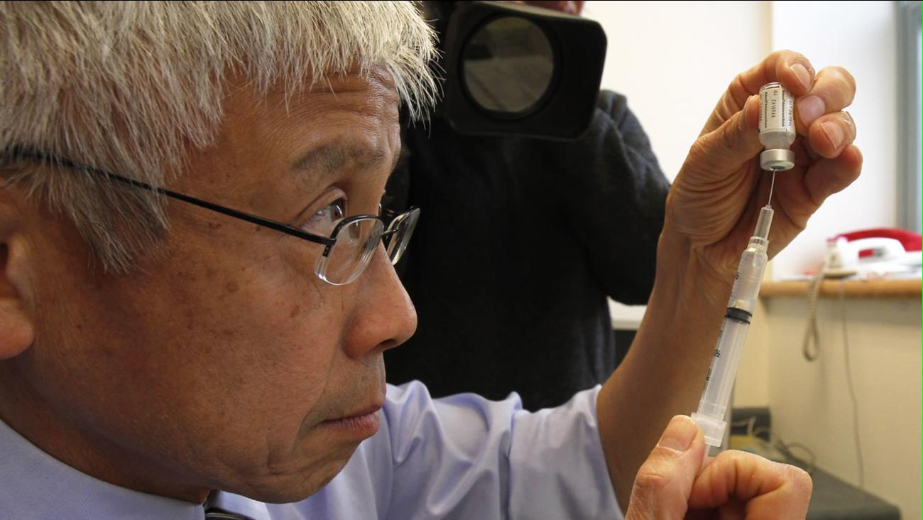 Man holding vaccine in syringe