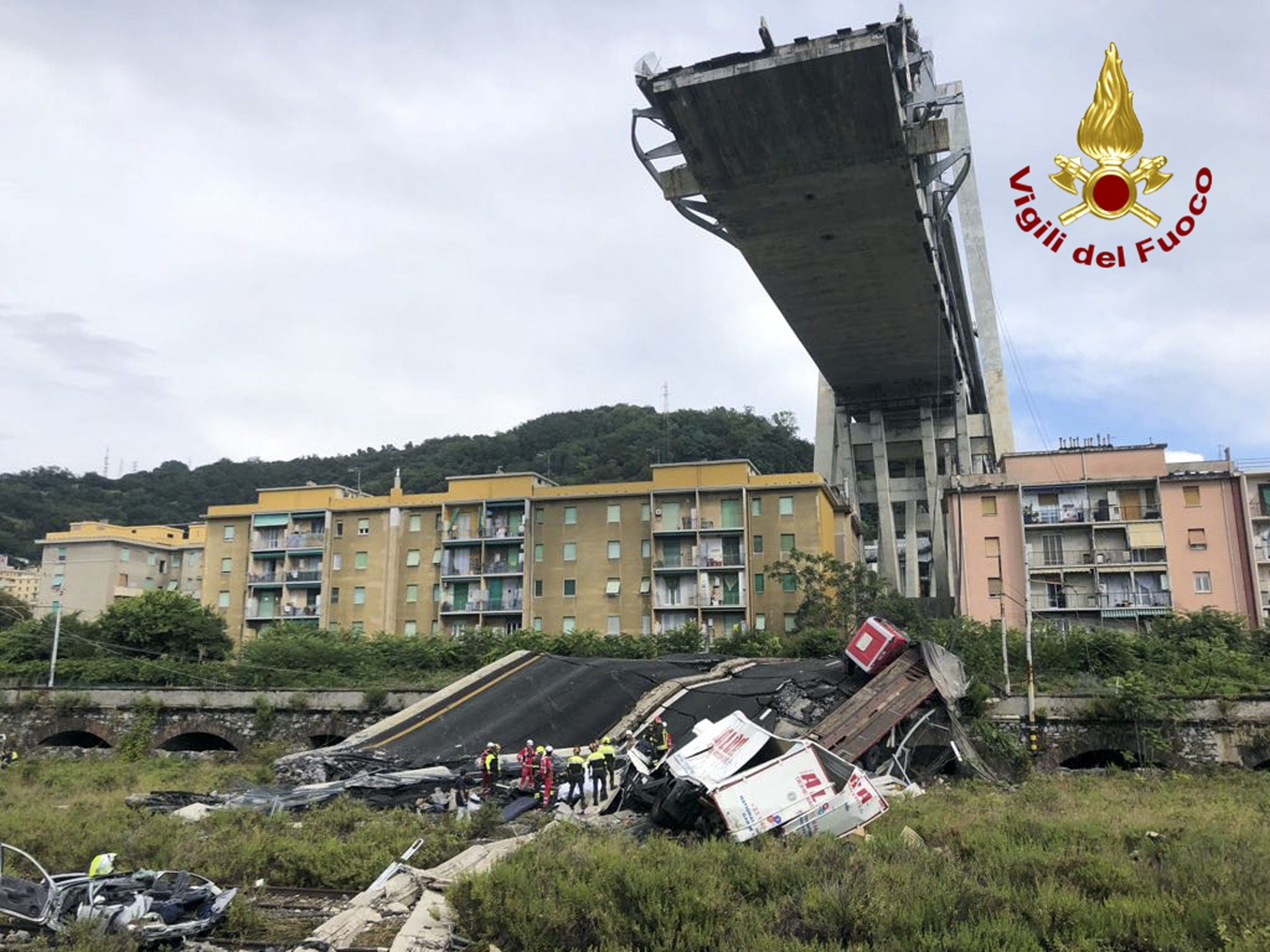 <div class='meta'><div class='origin-logo' data-origin='none'></div><span class='caption-text' data-credit='Vigili Del Fuoco via AP'>In this photo released by the Italian firefighters, firefighters work among the rubble of the collapsed Morandi highway bridge in Genoa, northern Italy, Tuesday, Aug. 14, 2018.</span></div>