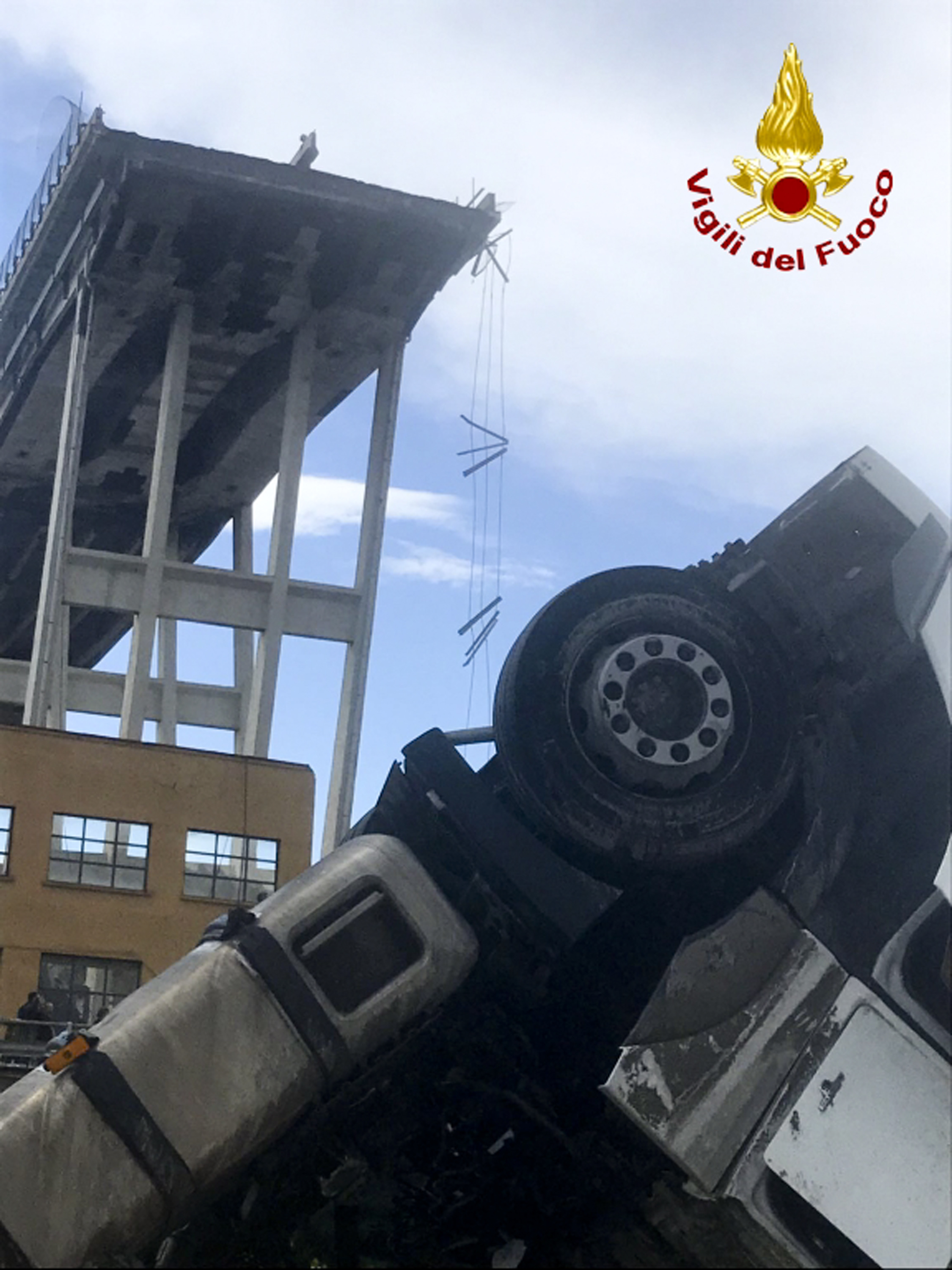 <div class='meta'><div class='origin-logo' data-origin='none'></div><span class='caption-text' data-credit='Vigili Del Fuoco via AP'>In this photo released by the Italian firefighters, a truck is seen under the partially collapsed Morandi highway bridge in Genoa, northern Italy, Tuesday, Aug. 14, 2018.</span></div>