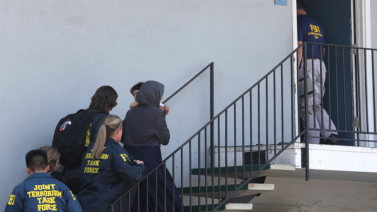 <div class='meta'><div class='origin-logo' data-origin='none'></div><span class='caption-text' data-credit='AP Photo/Rich Pedroncelli'>A woman carrying a child is escorted by authorities to an apartment following the arrest of a 45-year-old Iraqi refugee, Omar Ameen, Wednesday, in Sacramento.</span></div>