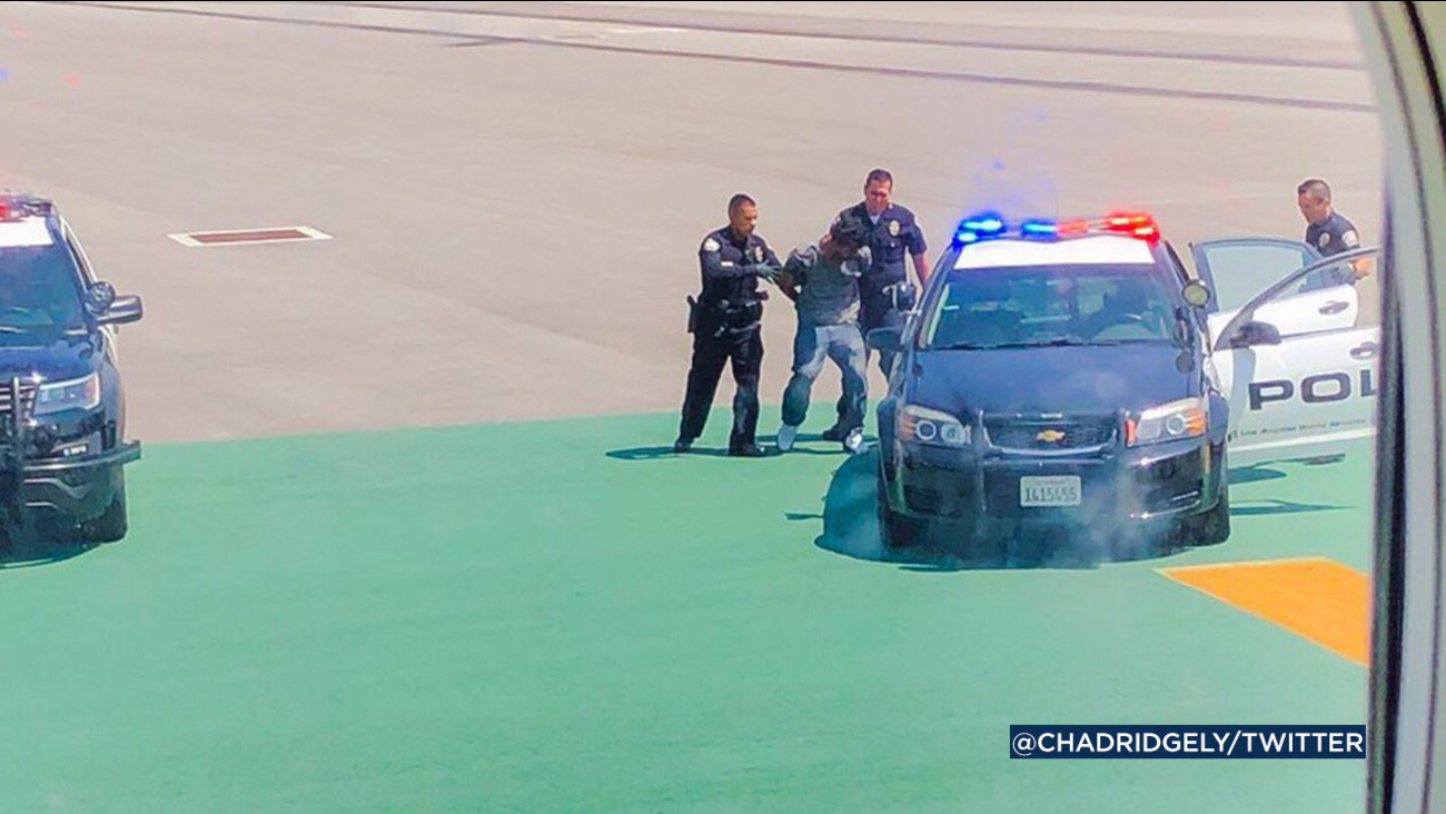 LAX police detained a man on the tarmac after he scaled an outer perimeter fence.