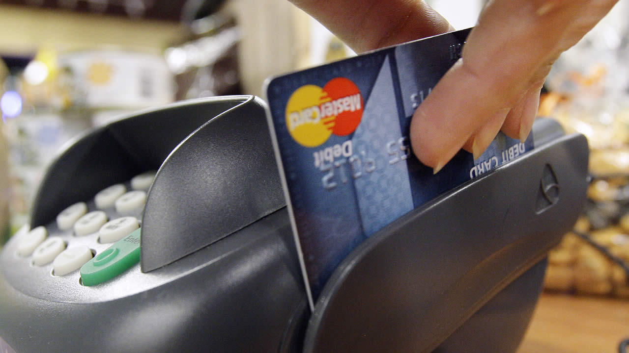 In this Nov. 2, 2009 file photo, a customer swipes a MasterCard debit card through a machine while checking out at a shop in Seattle. (AP Photo/Elaine Thompson, file)