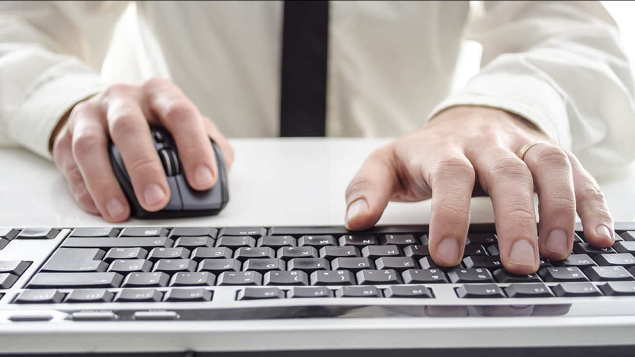 Person typing on a computer keyboard.