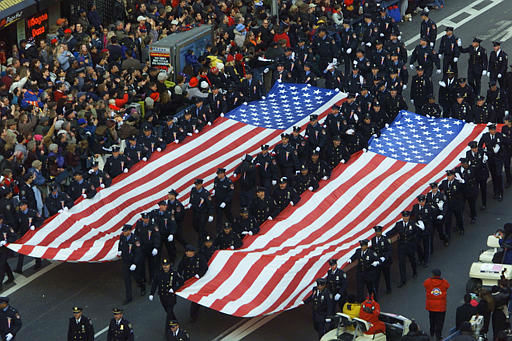 <div class='meta'><div class='origin-logo' data-origin='none'></div><span class='caption-text' data-credit=''>Police and other emergency workers hold two 54-foot flag banners, meant to represent the World Trade Center towers when seen from the air on Thursday, Nov. 22, 2001.</span></div>