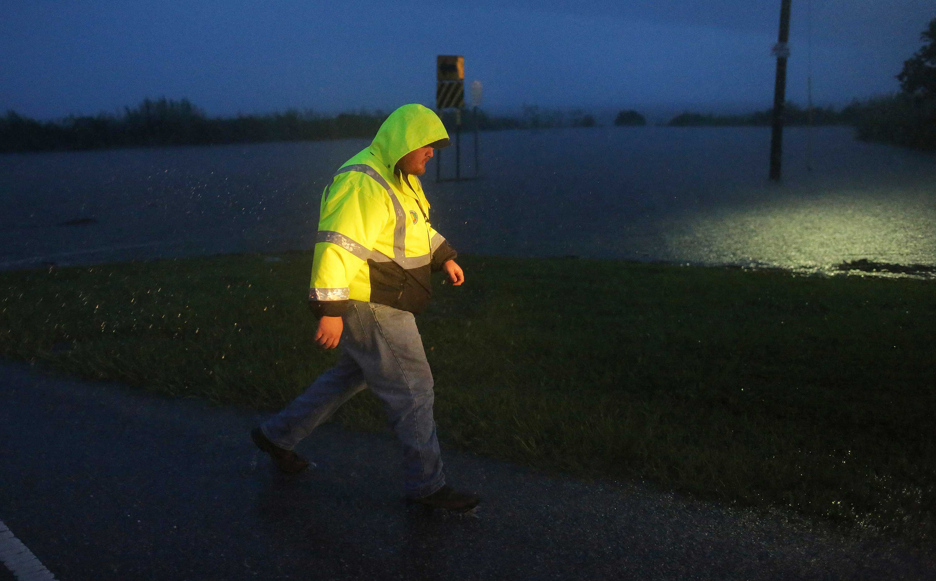 <div class='meta'><div class='origin-logo' data-origin='none'></div><span class='caption-text' data-credit='Dan Anderson/AP Photo'>A crew member with the Alabama Department of Transportation walks by a flooded parking lot on US Highway 98 in Spanish Fort, Ala. on Wednesday, Sept. 5.</span></div>