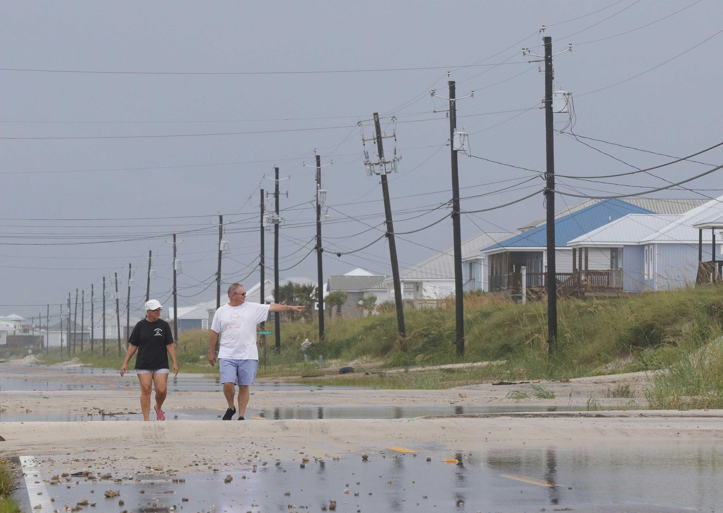 <div class='meta'><div class='origin-logo' data-origin='none'></div><span class='caption-text' data-credit='Dan Anderson/AP Photo'>Susan and Bill Jones walk through a road partially covered with sand from Tropical Storm Gordon on Wednesday, Sept. 5, 2018, in Dauphin Island, Ala.</span></div>