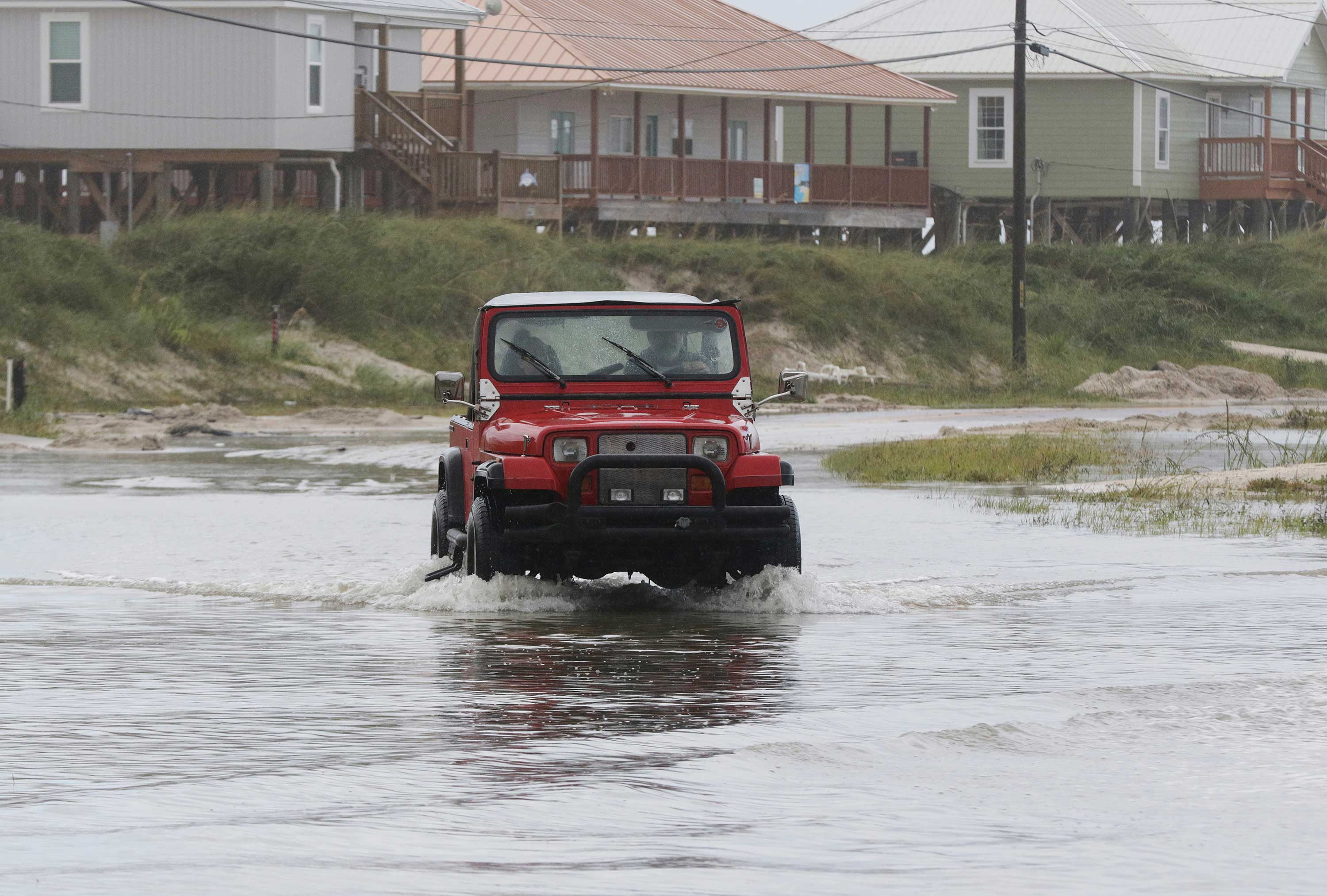 <div class='meta'><div class='origin-logo' data-origin='none'></div><span class='caption-text' data-credit='Dan Anderson/AP Photo'>A vehicle drives through a flooded street from Tropical Storm Gordon on Wednesday, Sept. 5, 2018 in Dauphin Island, Ala.</span></div>