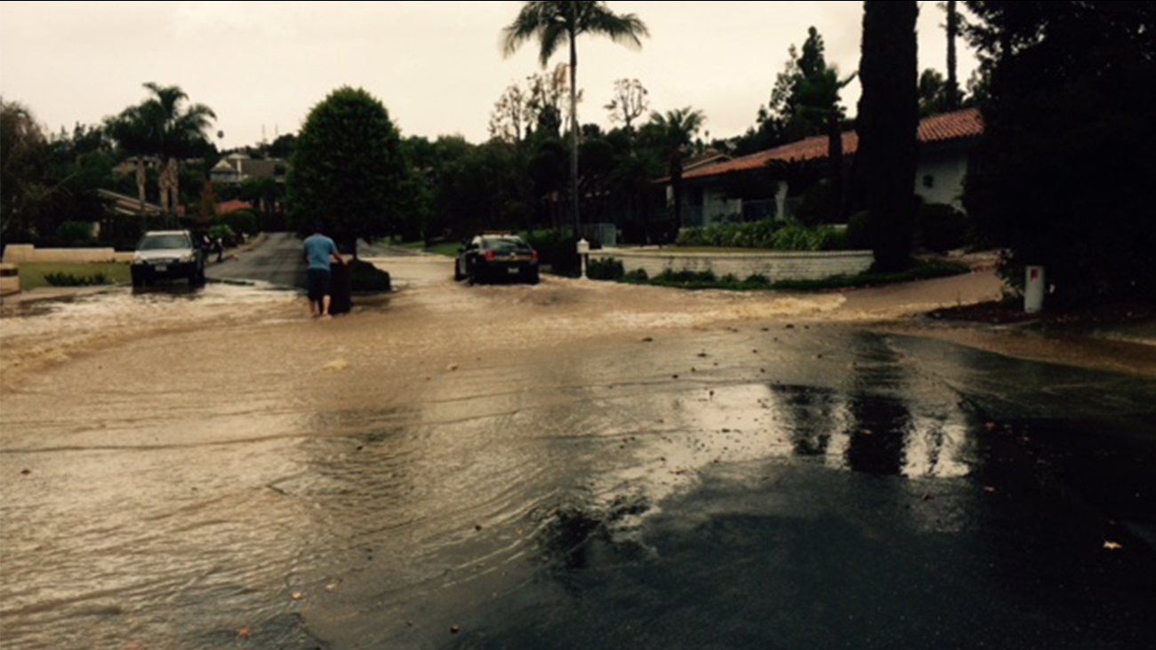 Water floods a street in Villa Park, where a water main broke on Sunday, Nov. 30, 2014.
