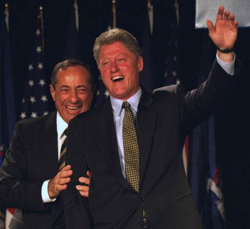"""<div class=""""meta image-caption""""><div class=""""origin-logo origin-image """"><span></span></div><span class=""""caption-text"""">President Bill Clinton waves from the stage at the Sheraton, New York Hotel as New York Governor Mario Cuomo helps to direct the president's gaze on Oct. 19, 1994.</span></div>"""