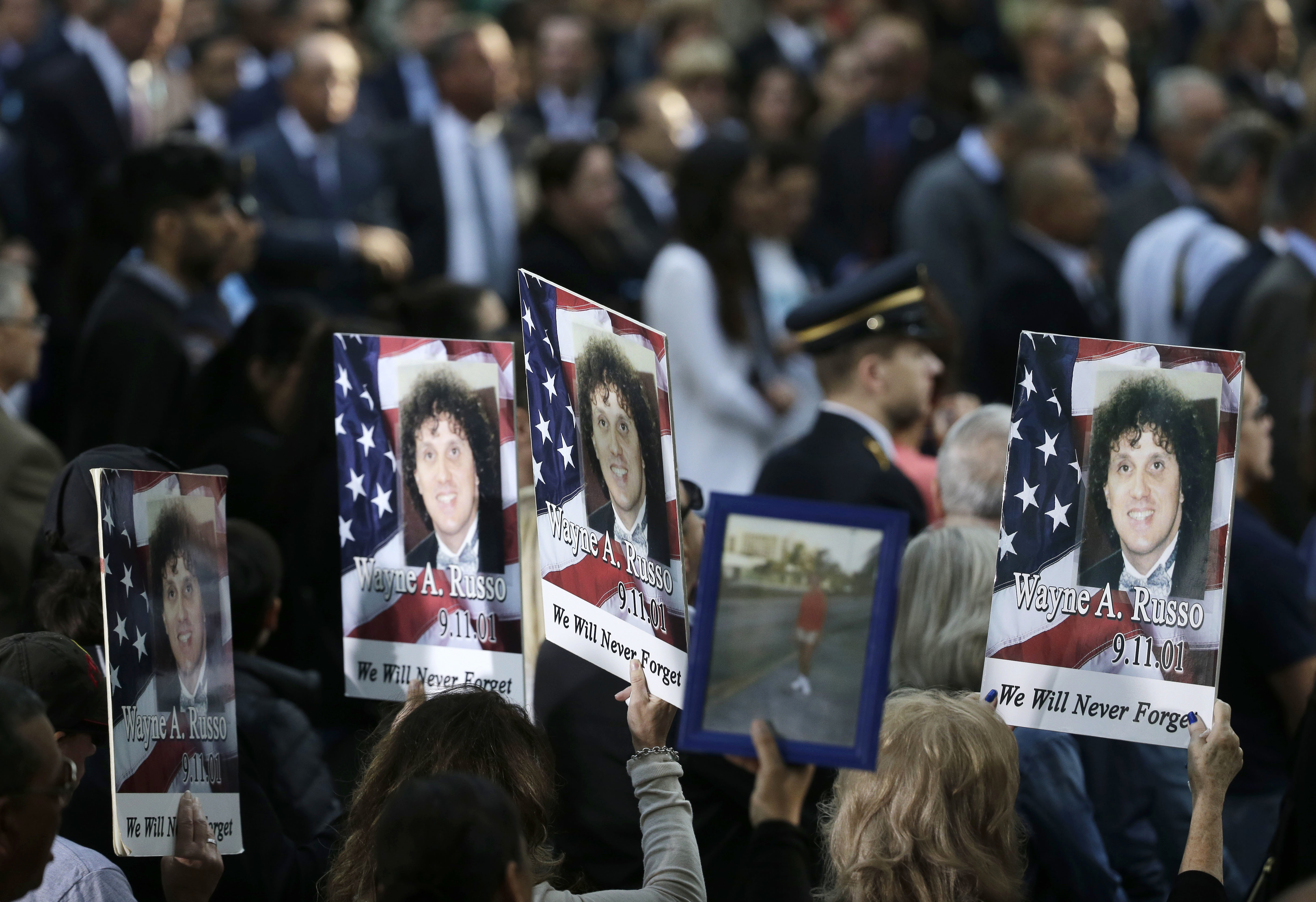"<div class=""meta image-caption""><div class=""origin-logo origin-image none""><span>none</span></div><span class=""caption-text"">People hold up signs with the names and pictures of victims of the 9/11 terrorist attacks during a ceremony at ground zero in New York, Monday, Sept. 11, 2017. (AP Photo/Seth Wenig)</span></div>"