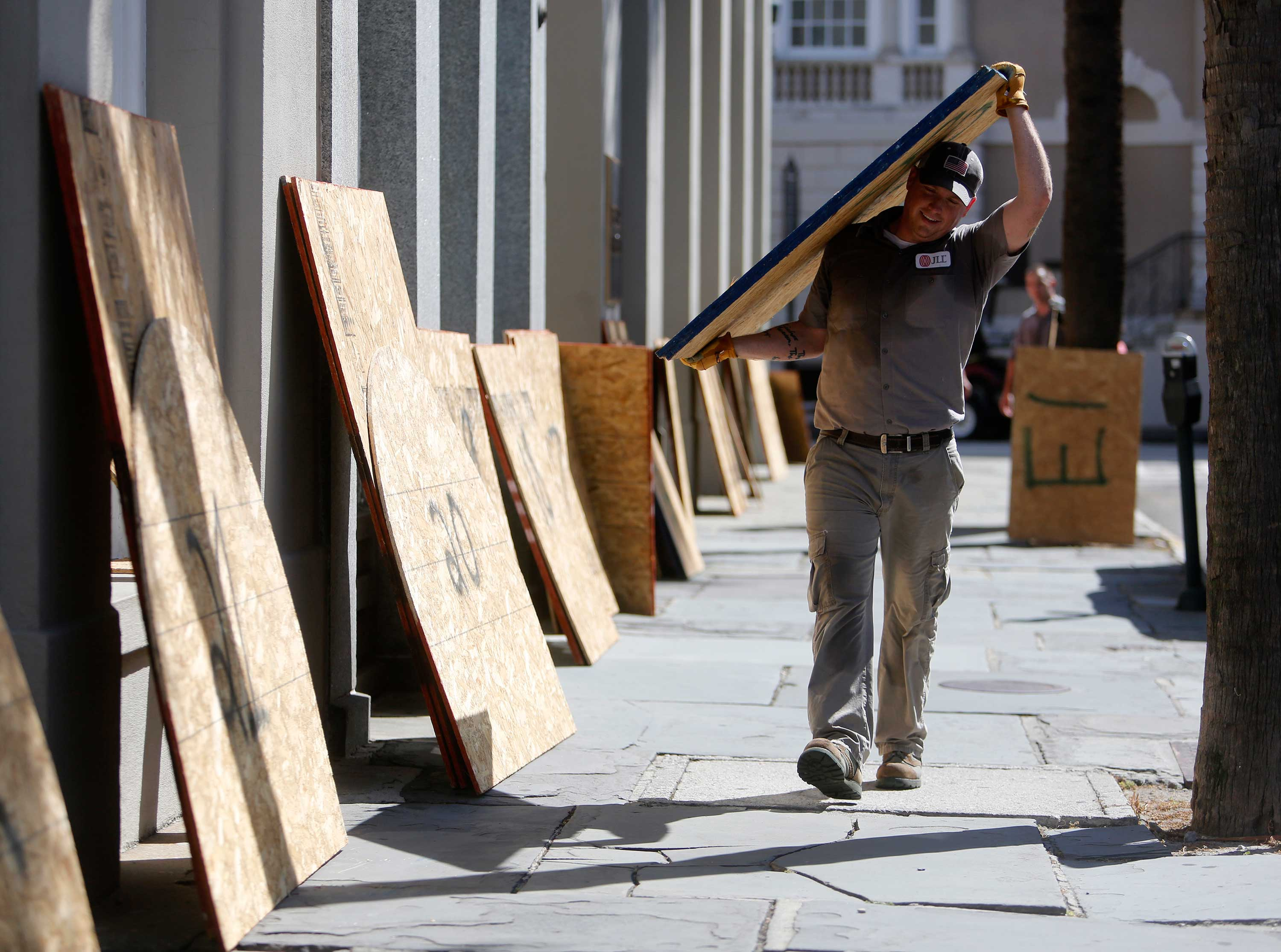 <div class='meta'><div class='origin-logo' data-origin='none'></div><span class='caption-text' data-credit='Mic Smith/AP Photo'>Preston Guiher carries a sheet of plywood as he prepares to board up a Wells Fargo bank in preparation for Hurricane Florence in downtown Charleston, S.C., Tuesday, Sept. 11, 2018.</span></div>