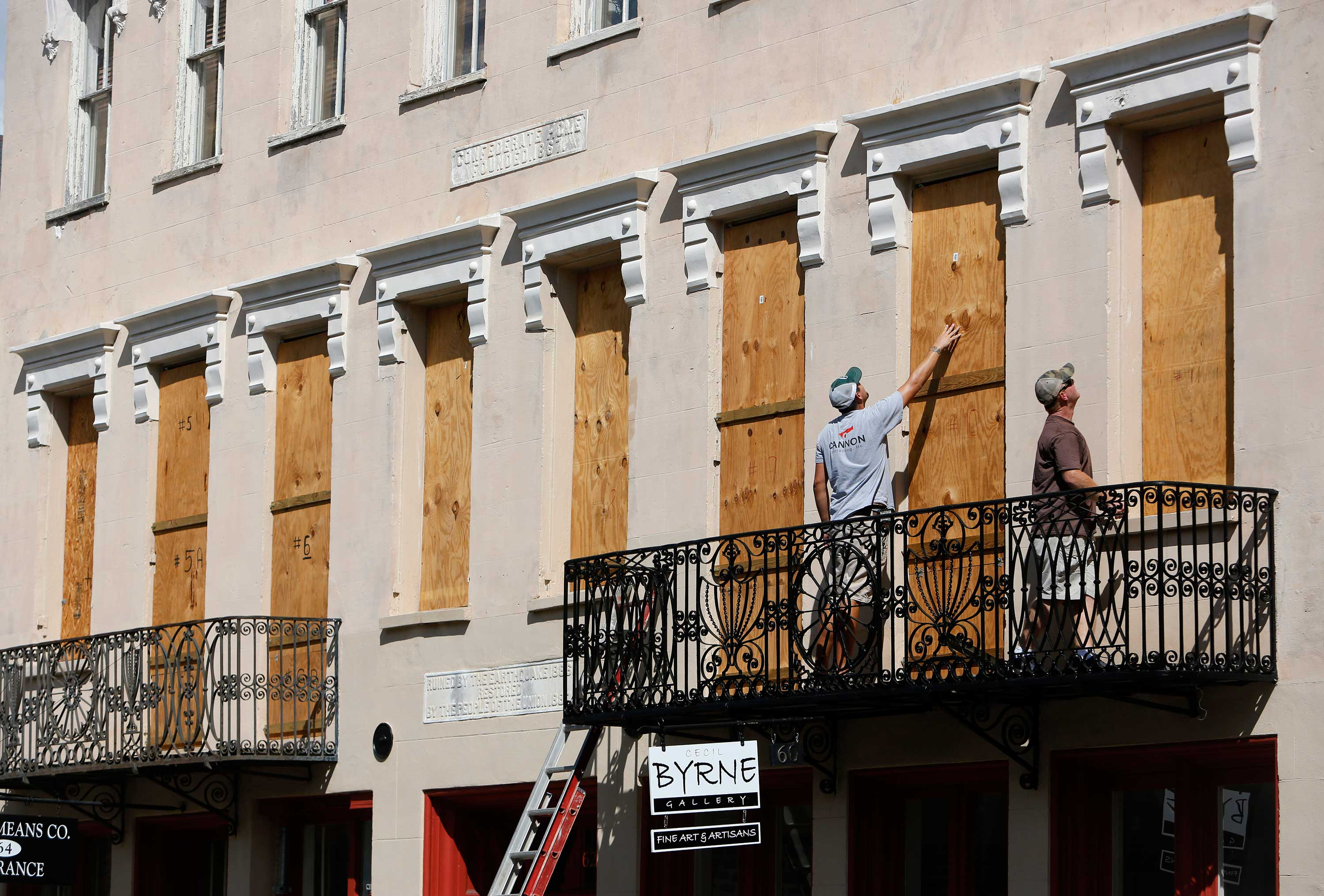 <div class='meta'><div class='origin-logo' data-origin='none'></div><span class='caption-text' data-credit='Mic Smith/AP Photo'>Derek Mundy, left, and Kris Crouse boards up the Confederate House in preparation for Hurricane Florence in downtown Charleston, S.C., Tuesday, Sept. 11, 2018.</span></div>