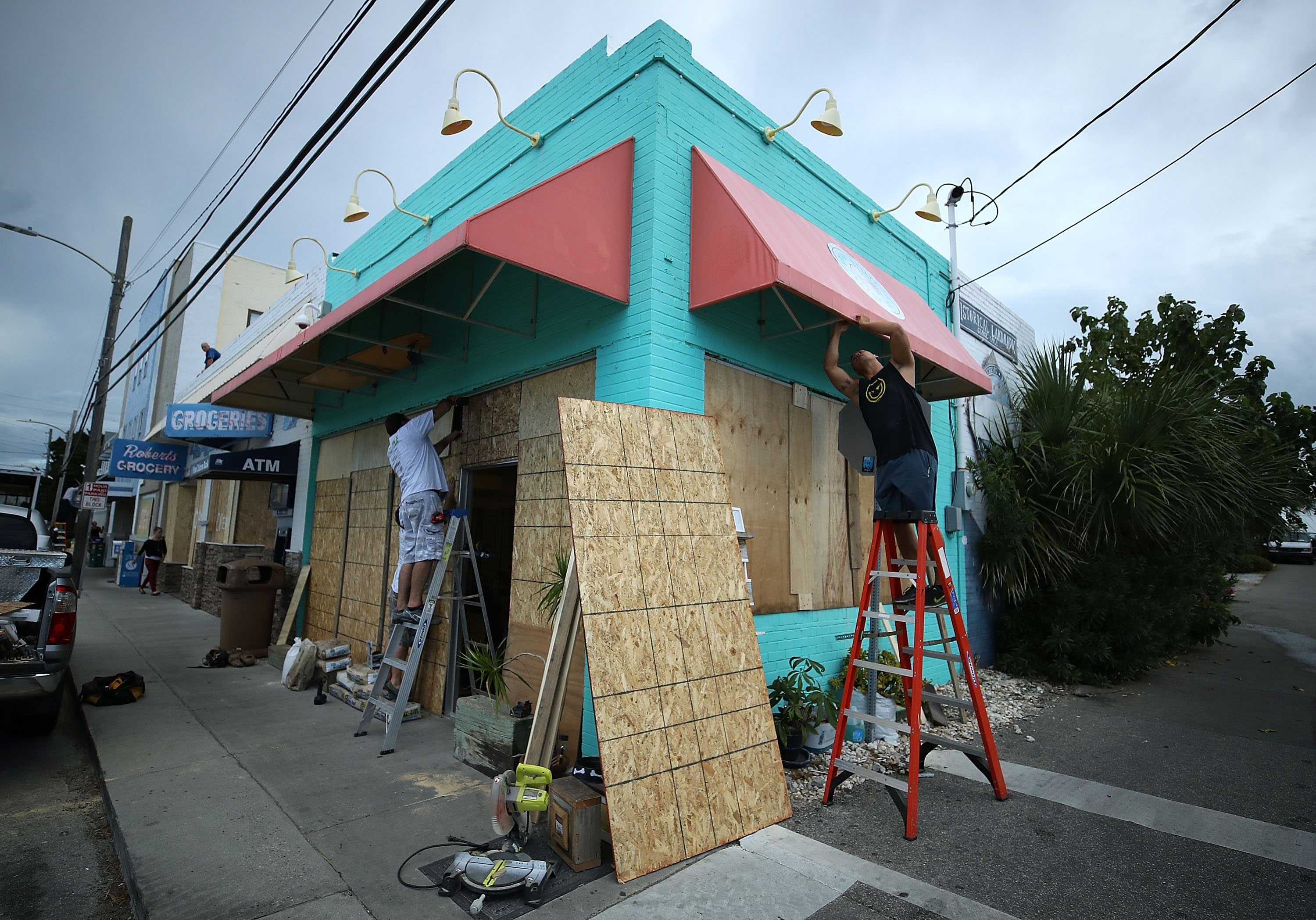 <div class='meta'><div class='origin-logo' data-origin='none'></div><span class='caption-text' data-credit='Mark Wilson/Getty Images'>Workers board up the Wrightsville Beach Art Co. while preparing for the arrival of Hurricane Florence on September 11, 2018 in Wrightsville Beach, N.C.</span></div>