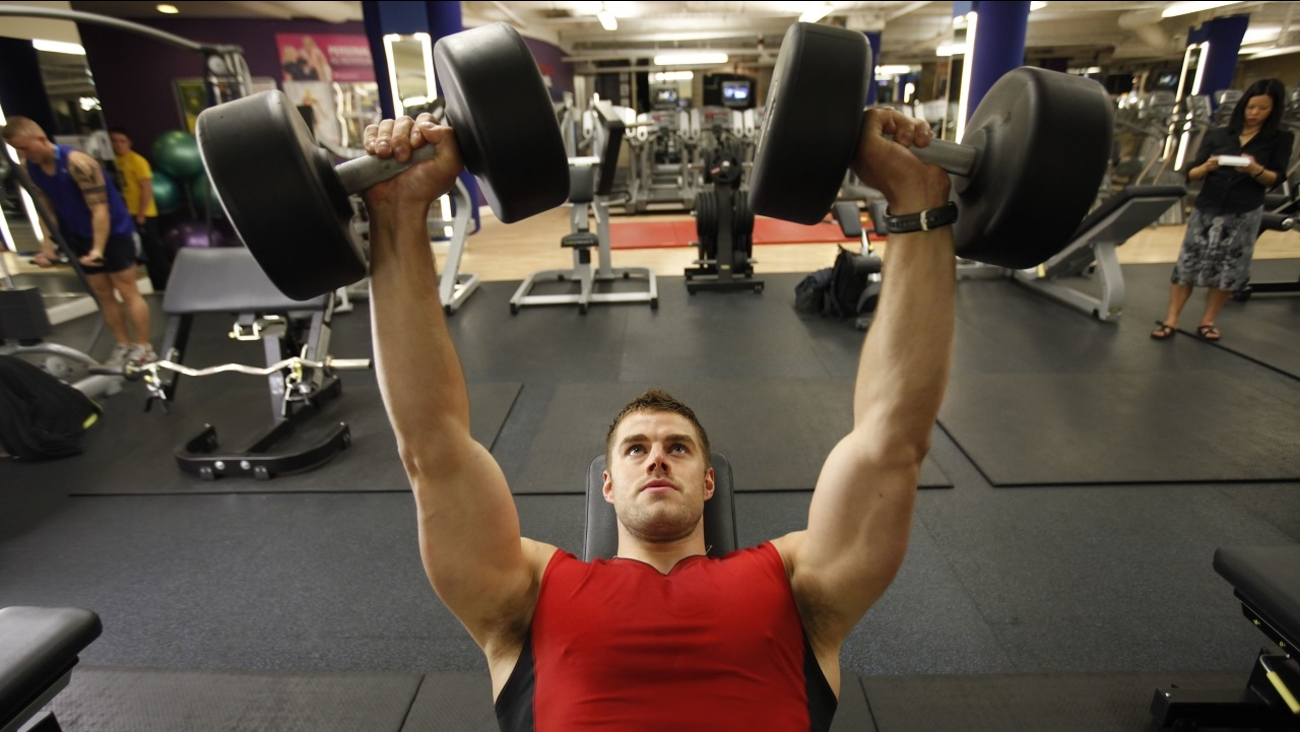 This photo shows a personal trainer, as he lifts weights during a training session at a gym.