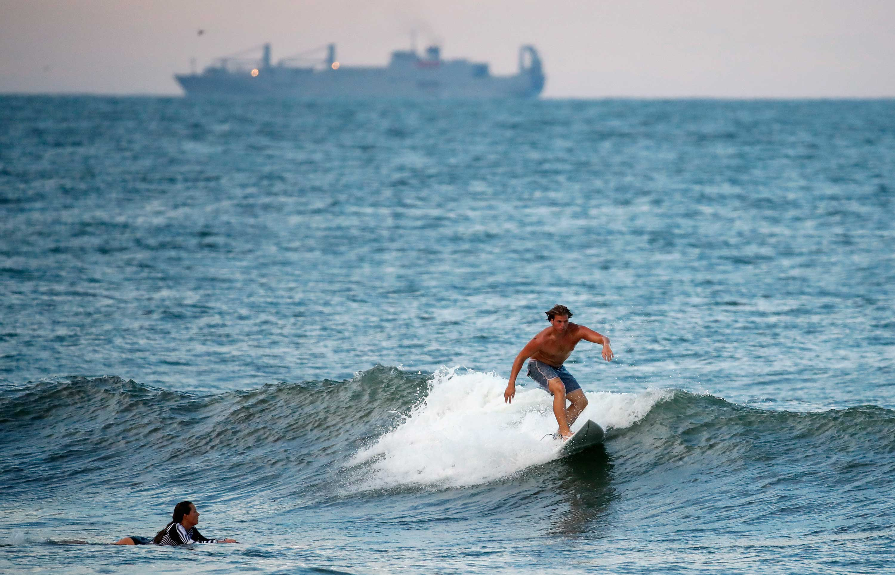 <div class='meta'><div class='origin-logo' data-origin='none'></div><span class='caption-text' data-credit='Alex Brandon/AP Photo'>A surfer catches a wave with a navy ship behind him, Tuesday, Sept. 11, 2018, in Virginia Beach, Va.</span></div>