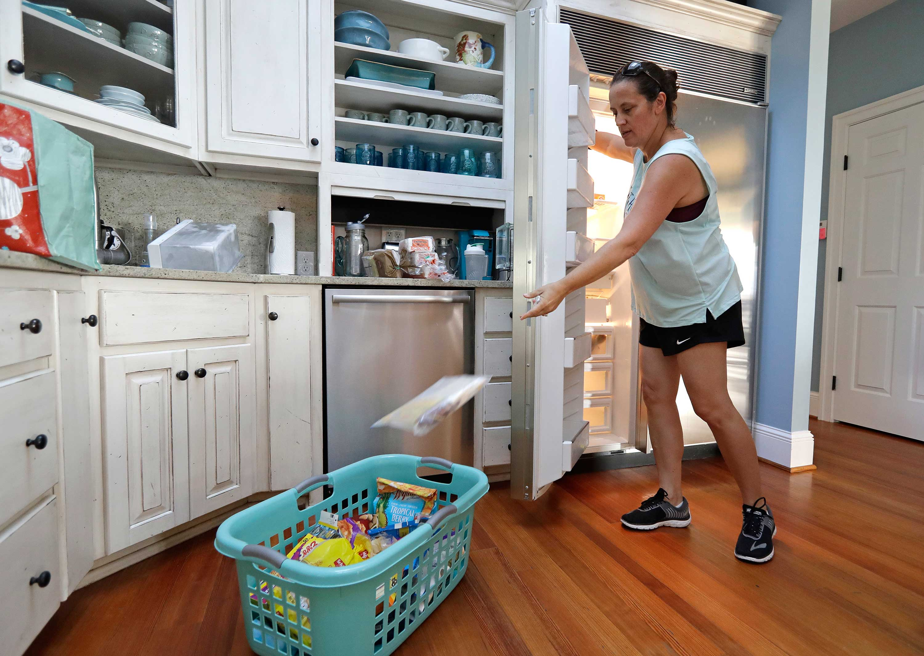 <div class='meta'><div class='origin-logo' data-origin='none'></div><span class='caption-text' data-credit='Chuck Burton/AP Photo'>Michelle Stober, of Cary, N.C., removes food from a freezer as she prepares their vacation home in advance of Hurricane Florence in Wrightsville Beach, N.C., Tuesday, Sept. 11.</span></div>