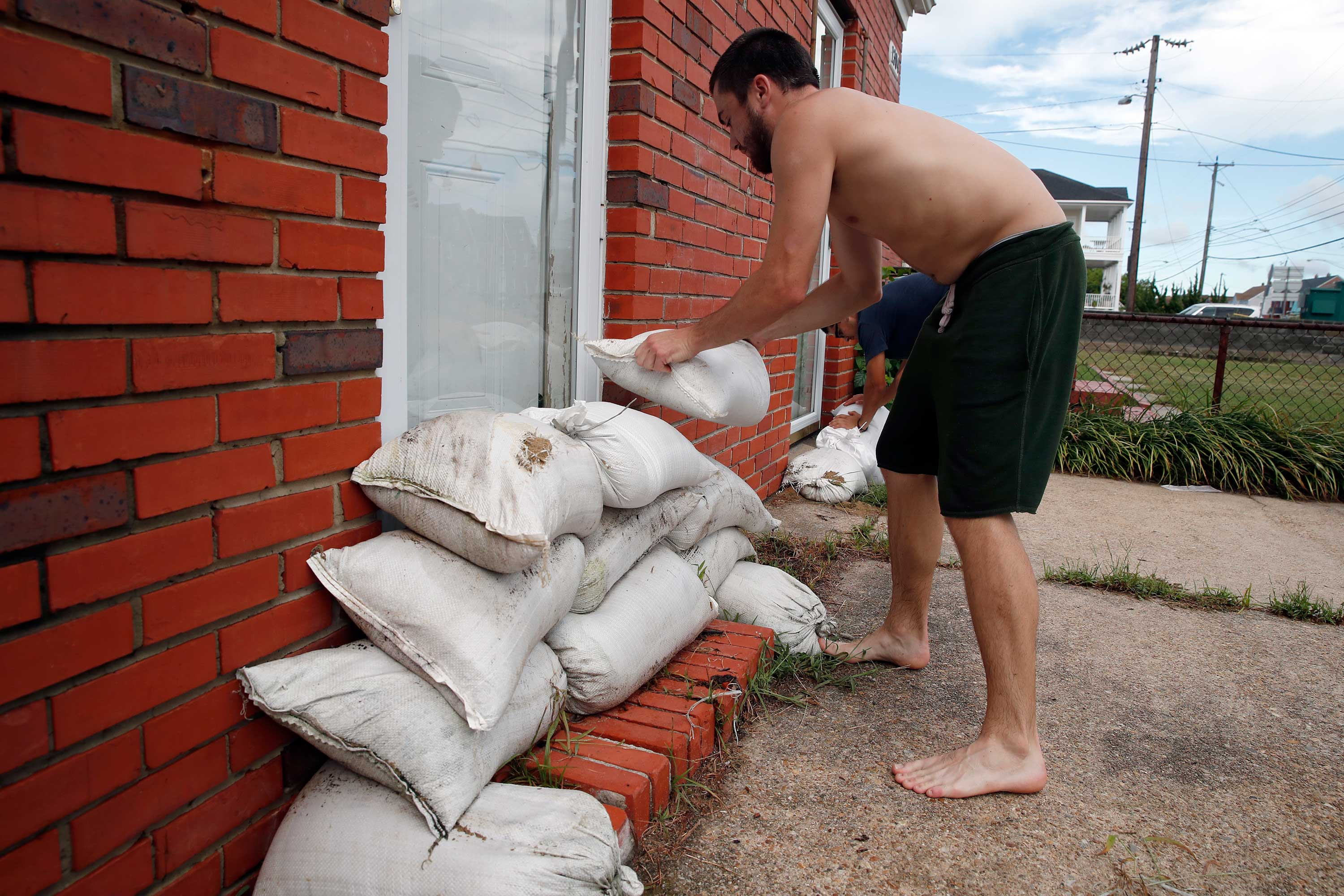 <div class='meta'><div class='origin-logo' data-origin='none'></div><span class='caption-text' data-credit='Alex Brandon/AP Photo'>Adam Bazemore places sandbags in the doorways, Tuesday, Sept. 11, 2018, in the Willoughby Spit area of Norfolk, Va., as he makes preparations for Hurricane Florence.</span></div>