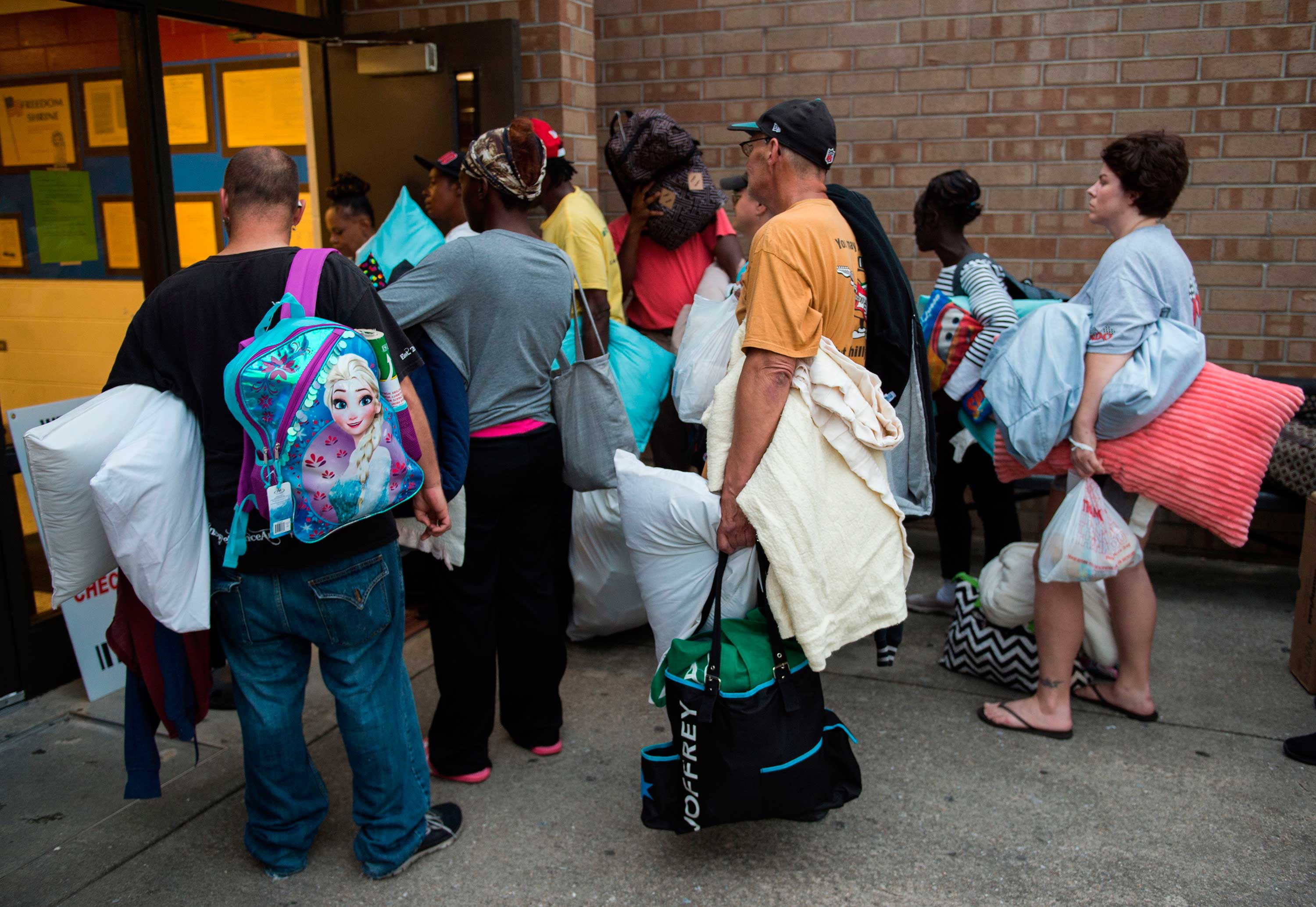 "<div class=""meta image-caption""><div class=""origin-logo origin-image none""><span>none</span></div><span class=""caption-text"">People line up to enter a hurricane shelter at Trask Middle School in wilmington, North Carolina, on September 11, 2018. (ANDREW CABALLERO-REYNOLDS/AFP/Getty Images)</span></div>"