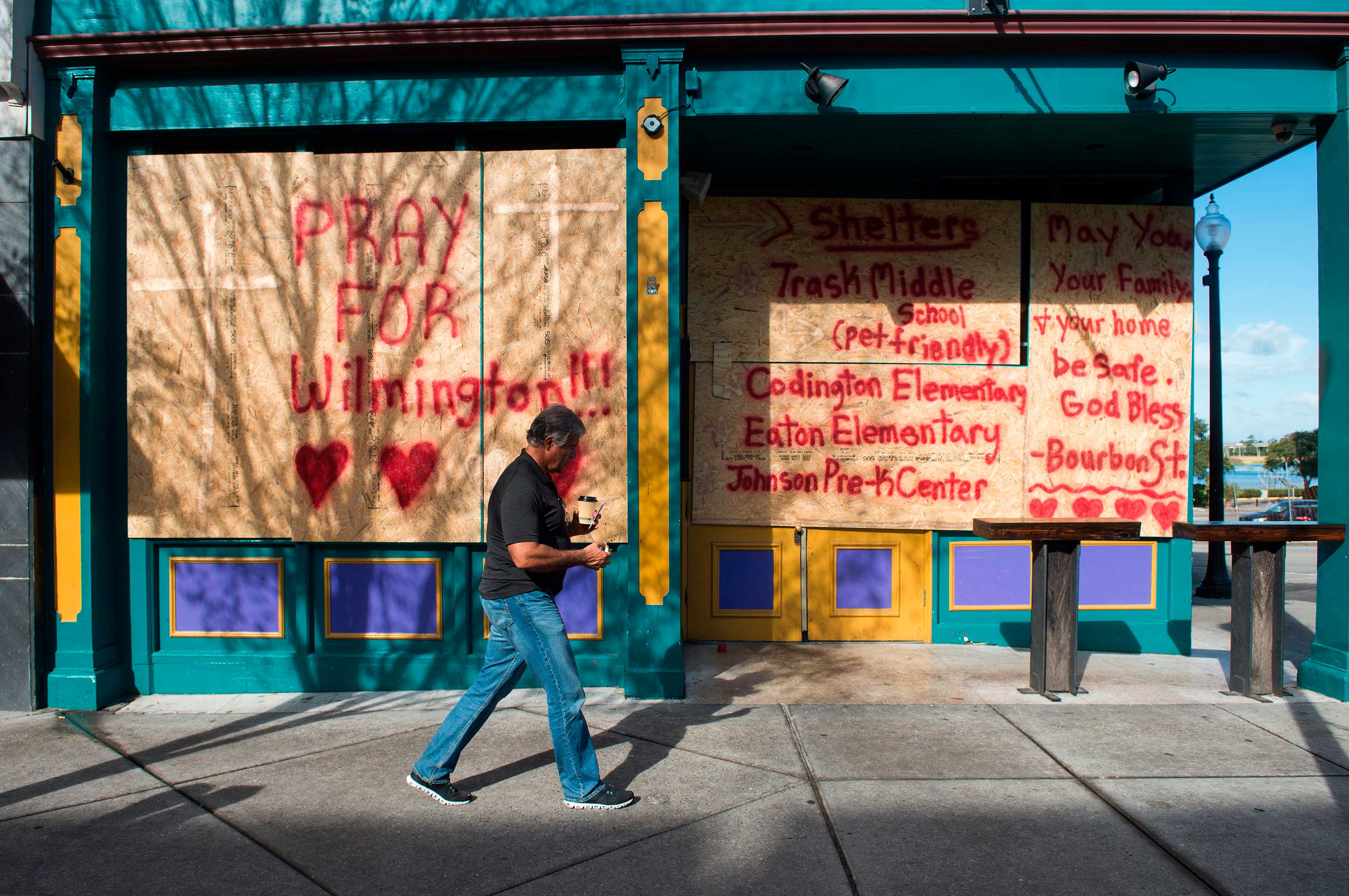 <div class='meta'><div class='origin-logo' data-origin='none'></div><span class='caption-text' data-credit='ANDREW CABALLERO-REYNOLDS/AFP/Getty Images'>A man walks past a boarded up shop in Wilmington, North Carolina on September 12, 2018.</span></div>