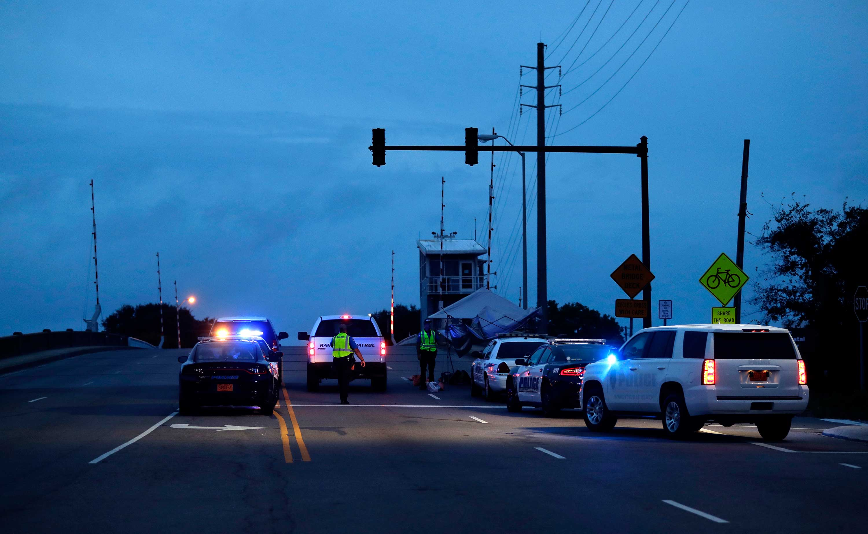 <div class='meta'><div class='origin-logo' data-origin='none'></div><span class='caption-text' data-credit='Chuck Burton/AP Photo'>Police man a road block near a drawbridge to Wrightsville Beach, N.C., as Hurricane Florence threatens the coast Thursday, Sept. 13, 2018.</span></div>