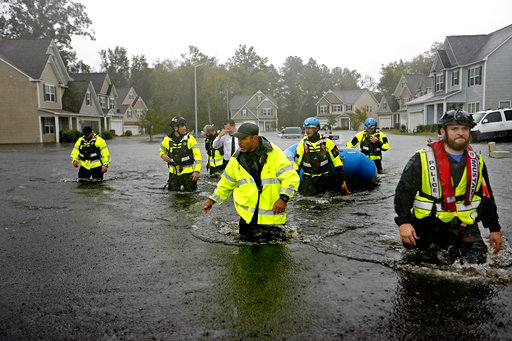 <div class='meta'><div class='origin-logo' data-origin='AP'></div><span class='caption-text' data-credit='AP Photo/David Goldman'>Members of the North Carolina Task Force urban search and rescue team wade through a flooded neighborhood looking for residents in Fayetteville, N.C., Sunday, Sept. 16, 2018.</span></div>