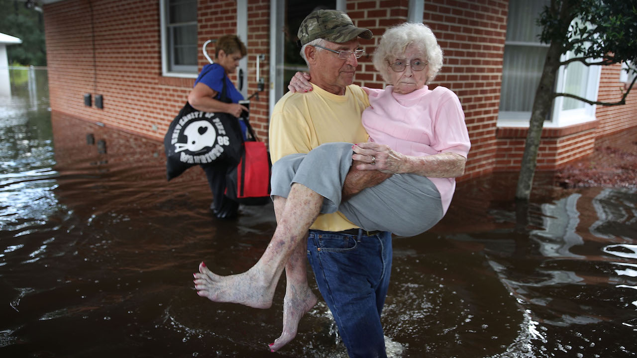 <div class='meta'><div class='origin-logo' data-origin='Creative Content'></div><span class='caption-text' data-credit='Joe Raedle/Getty Images'>Bob Richling carries Iris Darden as water from the Little River starts to seep into her home on September 17, 2018, in Spring Lake, North Carolina.</span></div>