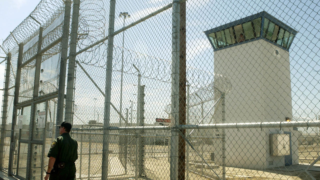 A correctional officer walks near a gate, which is one of two entrances into Kern Valley State Prison Tuesday, June 14, 2005, in Delano, Calif.