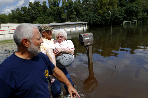<div class='meta'><div class='origin-logo' data-origin='AP'></div><span class='caption-text' data-credit='AP Photo/David Goldman'>Bob Richling carries Iris Darden, 84, into her flooded home joined by Darden's son, David Darden Jr., in Spring Lake, N.C., Monday, Sept. 17, 2018.</span></div>