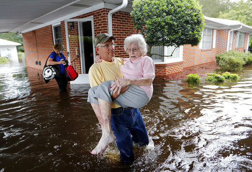 <div class='meta'><div class='origin-logo' data-origin='AP'></div><span class='caption-text' data-credit='AP Photo/David Goldman'>Bob Richling carries Iris Darden, 84, out of her flooded home as her daughter-in-law, Pam Darden, gathers her belongings in Spring Lake, N.C., Monday, Sept. 17, 2018.</span></div>