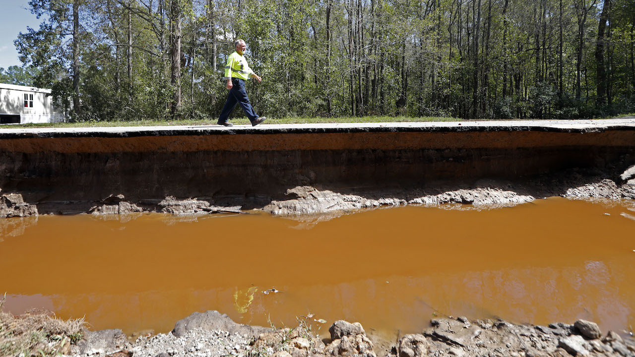 <div class='meta'><div class='origin-logo' data-origin='AP'></div><span class='caption-text' data-credit='AP Photo/Gerald Herbert'>South Carolina Public Works employee Danny Causey walks past a piece of roadway that was washed out by flooding from Hurricane Florence in Allsbrook, S.C., Tuesday, Sept. 18, 2018.</span></div>
