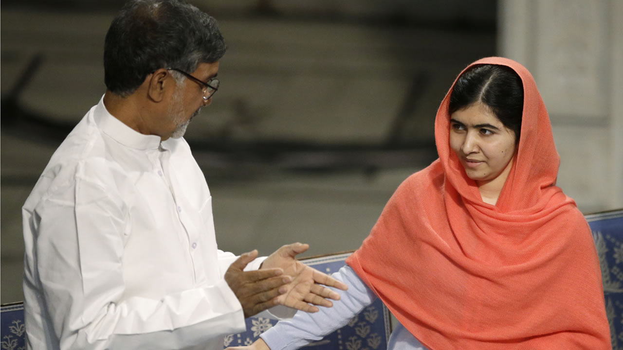 Nobel Peace Prize winner Malala Yousafzai from Pakistan, reaches out to joint winner Kailash Satyarthi from India during the Nobel Peace Prize award ceremony in Oslo.