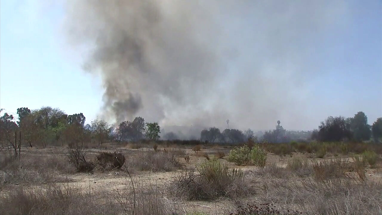 A brush fire burned at the bottom of a river in Corona near the Norco border.