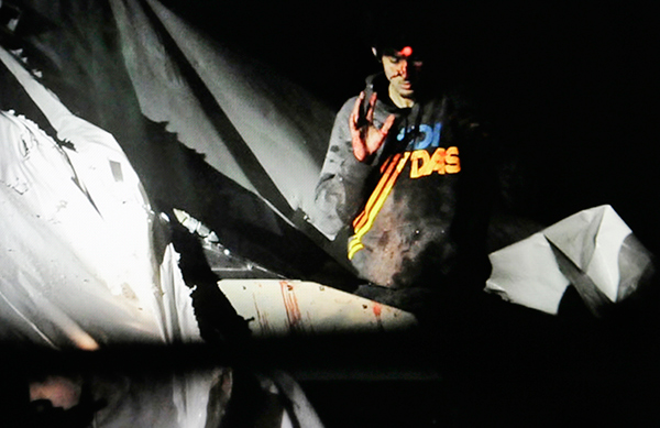In this April 19, 2013 photo, Boston Marathon bombing suspect Dzhokhar Tsarnaev, bloody and disheveled with the red dot of a rifle laser sight on his forehead, raises his hand from inside a boat at the time of his capture by law enforcement authorities.