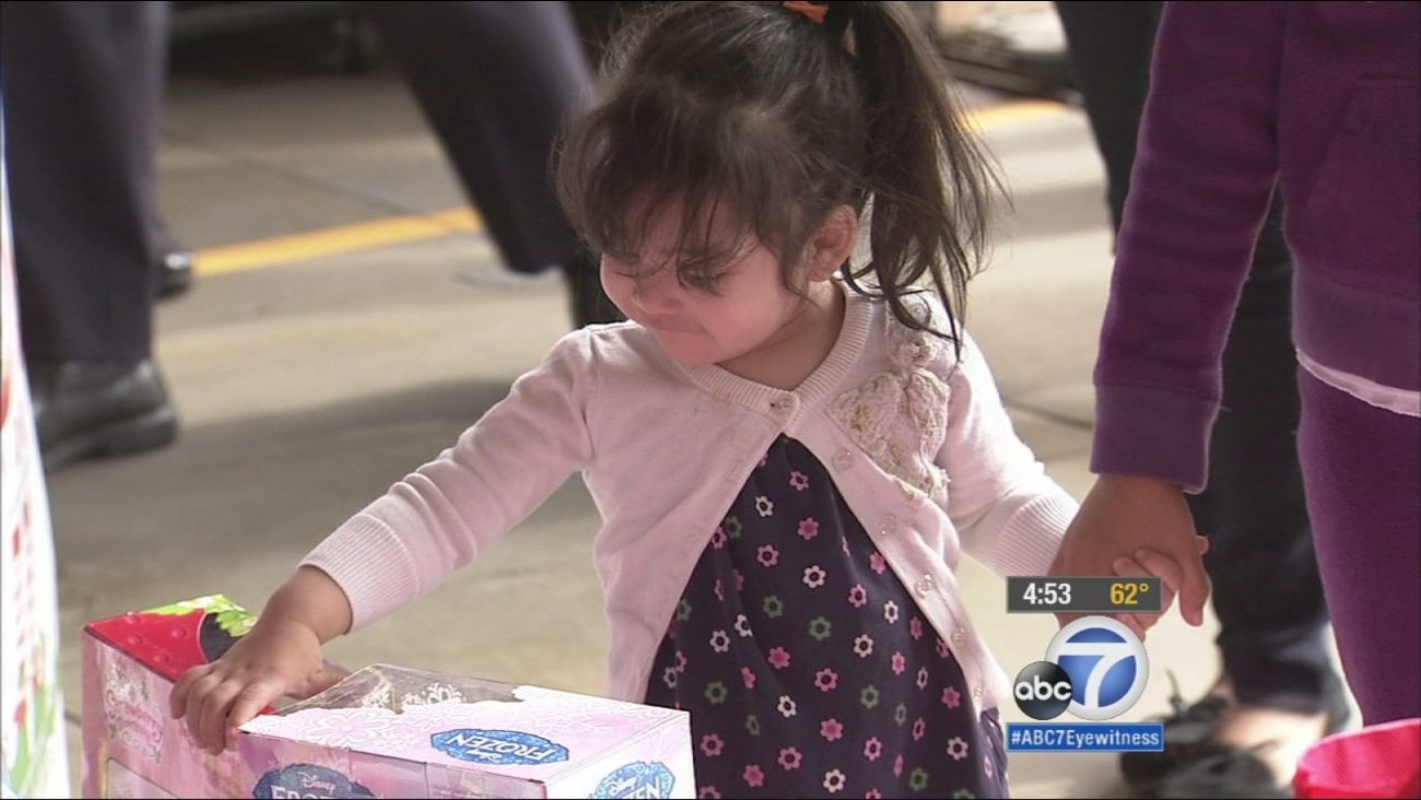 Blanca Rodriguez's daughter receives a toy from Spark of Love.