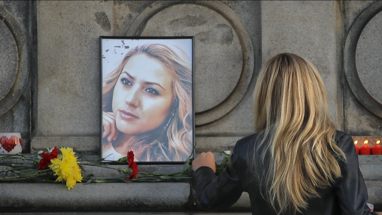 A woman places flowers next to a portrait of slain television reporter Viktoria Marinova during a vigil at the Liberty Monument in Ruse, Bulgaria, Monday, Oct. 8, 2018.