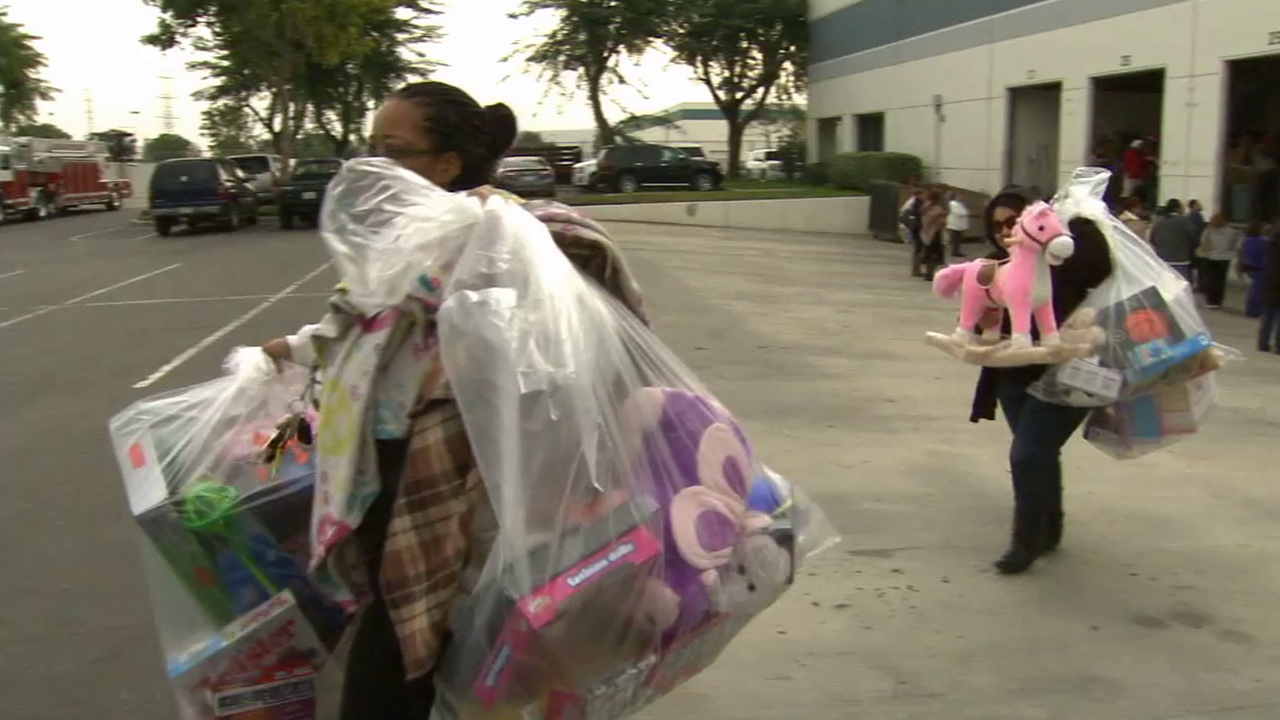 Two women walk away with toys donated to ABC7's Spark of Love toy drive on Saturday, Dec. 20, 2014.