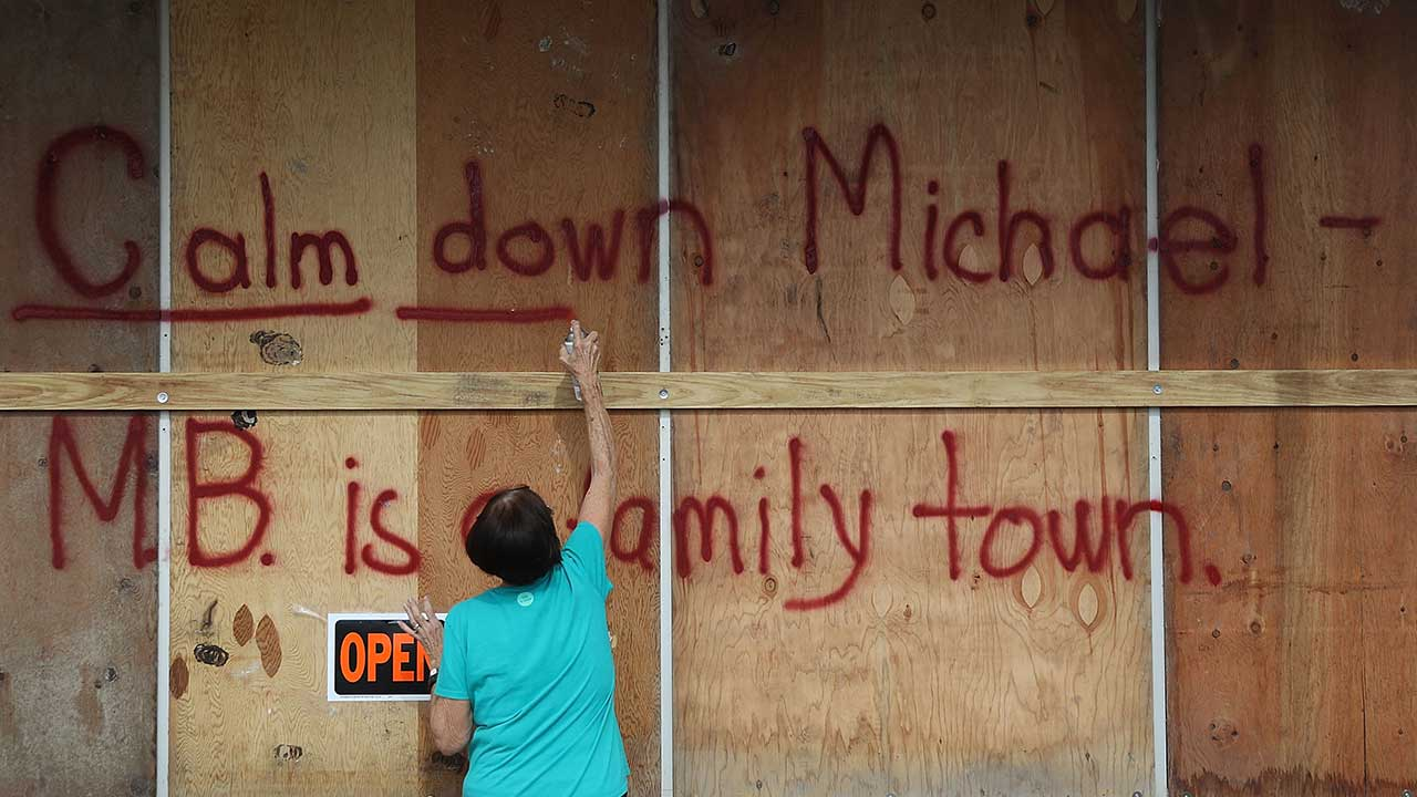 <div class='meta'><div class='origin-logo' data-origin='none'></div><span class='caption-text' data-credit='Joe Raedle/Getty Images'>Carol Cathey spray paints the words 'Calm down Michael' on the plywood over her daughter's business on October 9, 2018 in Mexico Beach, Florida.</span></div>